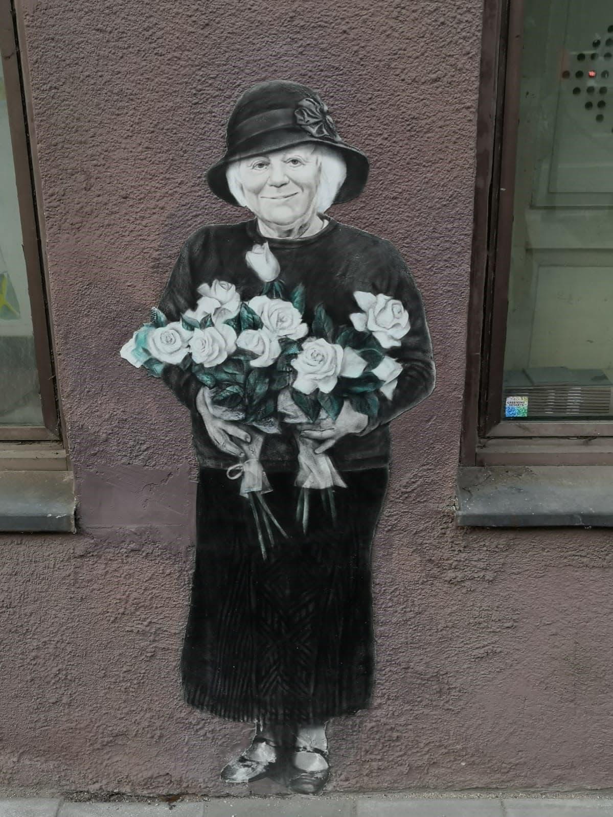 Katutaideteos, jossa mummo kukkia kädessään.