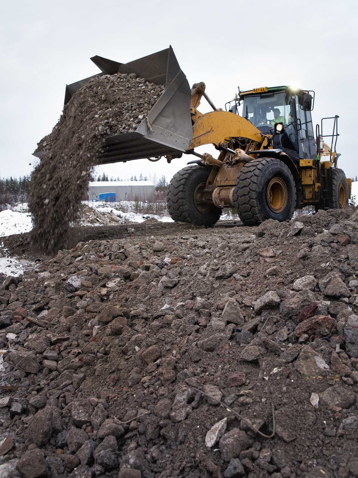Kauhakuormaaja levittää betonimursketta tiepohjaan.