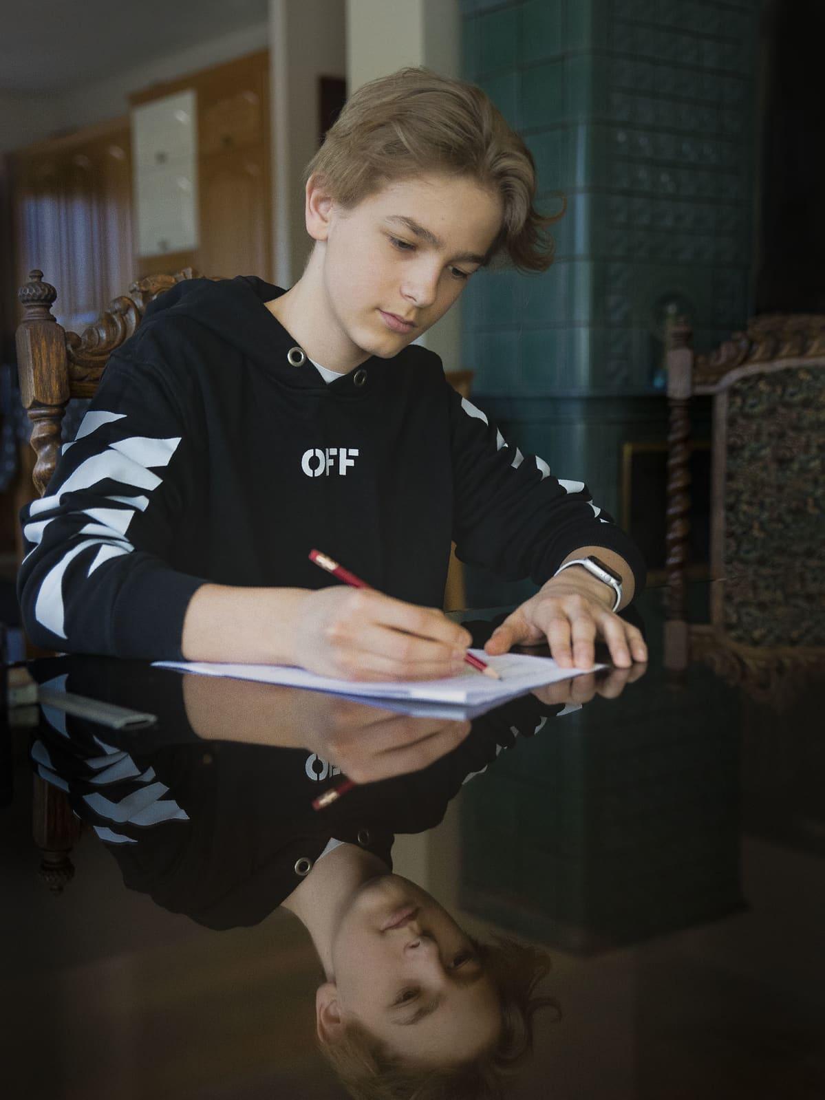 Oppilas tekee etäkoulussa tehtäviä kotonaan.
