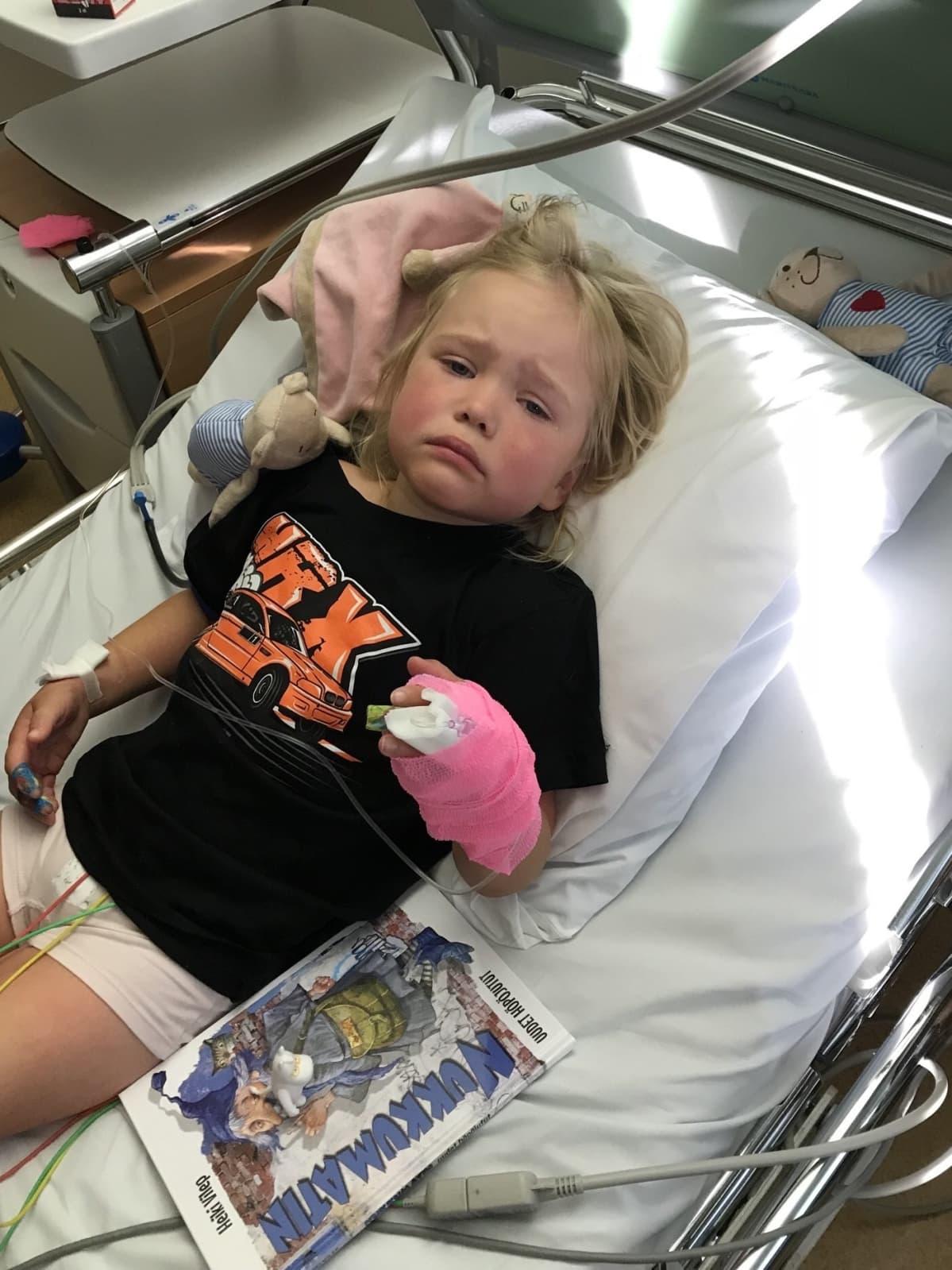 Lapsi makaa sairaalasängyssä ja on kiinni monitoreissa.