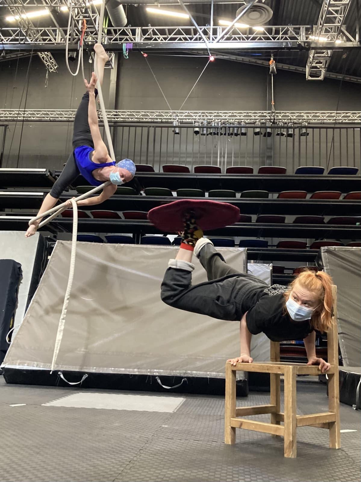Sirkuslaiset harjoittelevat temppujaan. Valpuri Kaarninen tekee spagaatin käydestä roikkuen ja Rosa-Maria Autio seisoo käsillään pyörittäen kangasta jalkojensa päällä.