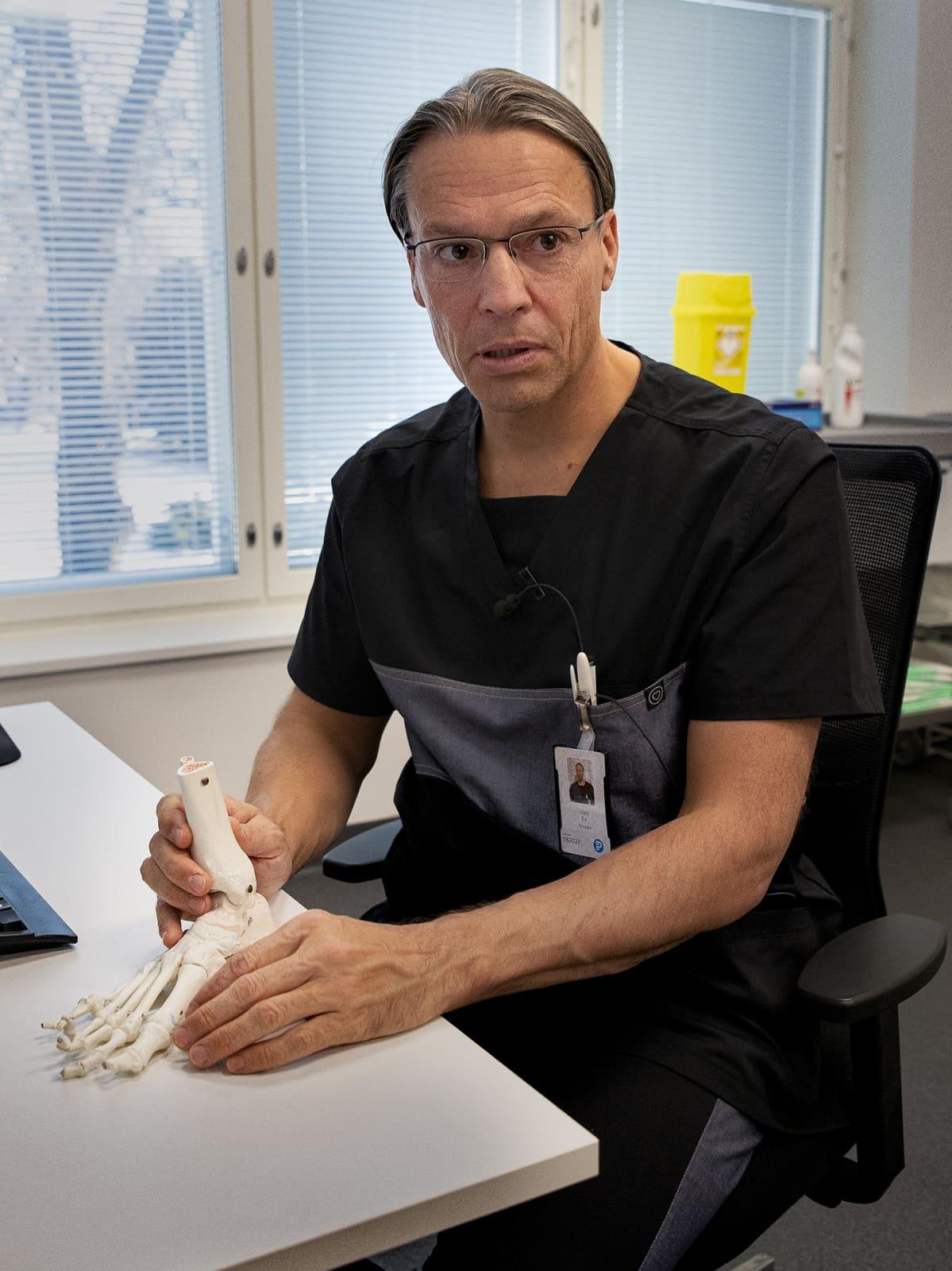 Ortopedi Jussi Elo esittelee jalkaterän luurankoa.
