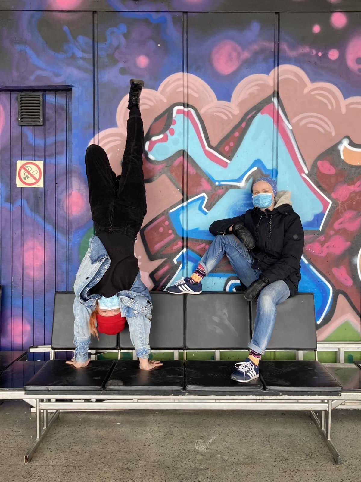 Valpuri Kaarninen istuu penkillä ja Rosa-Maria Autio seisoo käsillään hänen vieressään. Taustalla on sirkuksen iloisenvärinen graffitiseinä.