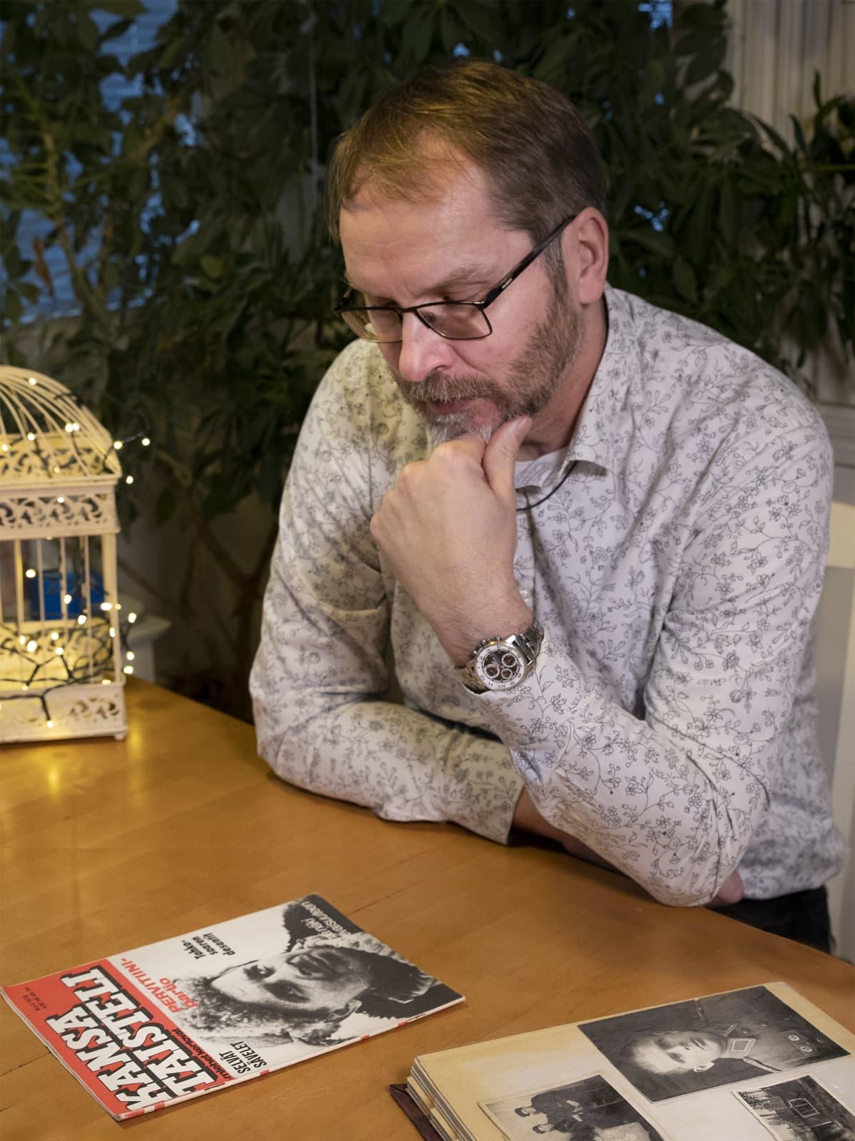 Mika Koivunen istuu pöydän äärellä ja katselee Kansa taisteli -lehteä.