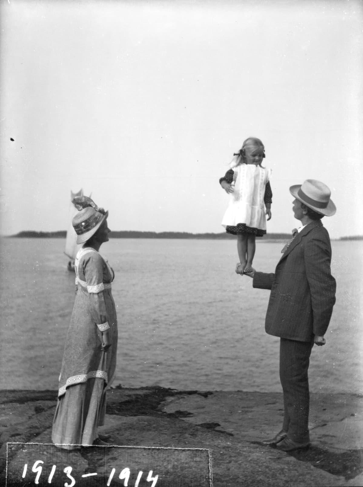 Tyttö seisoo isänsä kämmenellä
