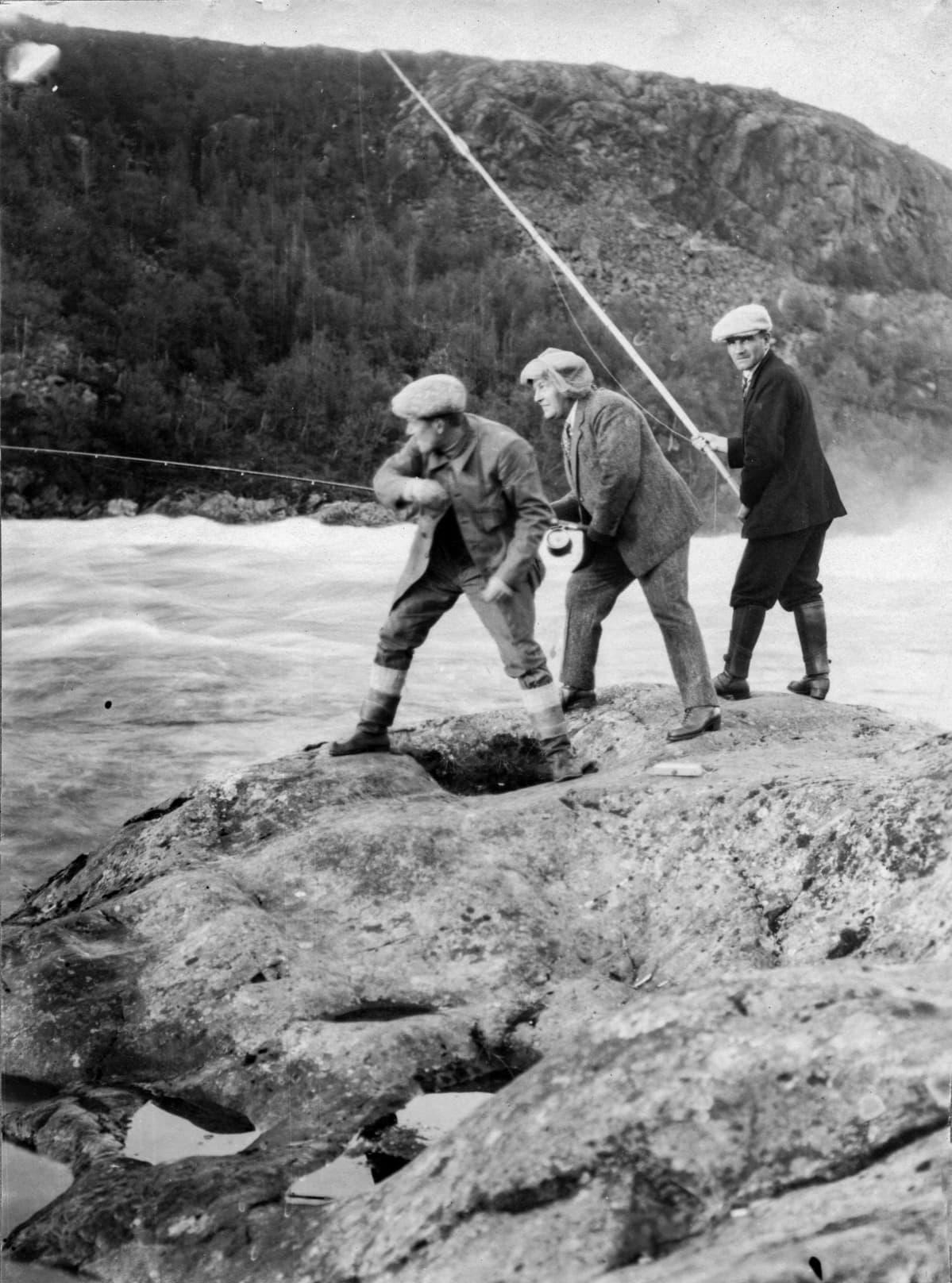 Kolme turistia kalastamassa Paatsjoen Kolttakönkään rantakalliolla, Petsamo kesällä 1924.