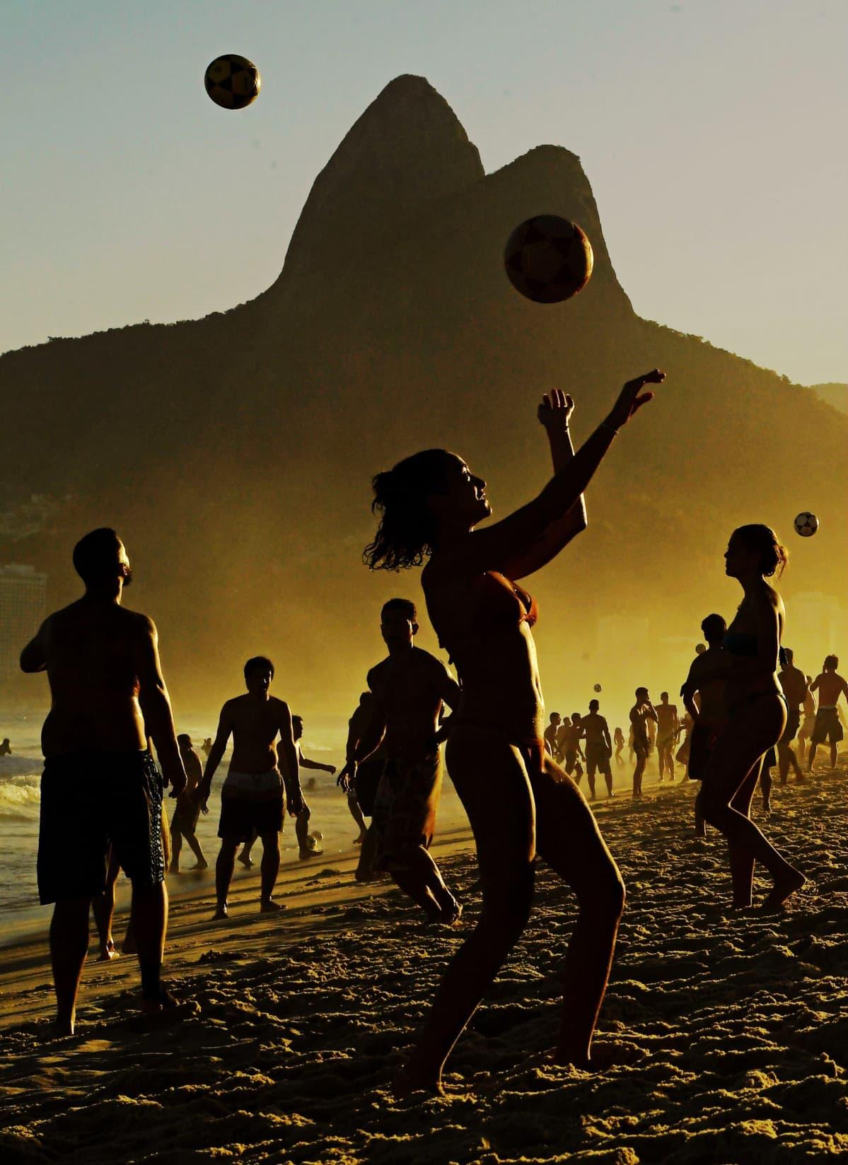 Ihmiset pelaavat palloa rannalla.