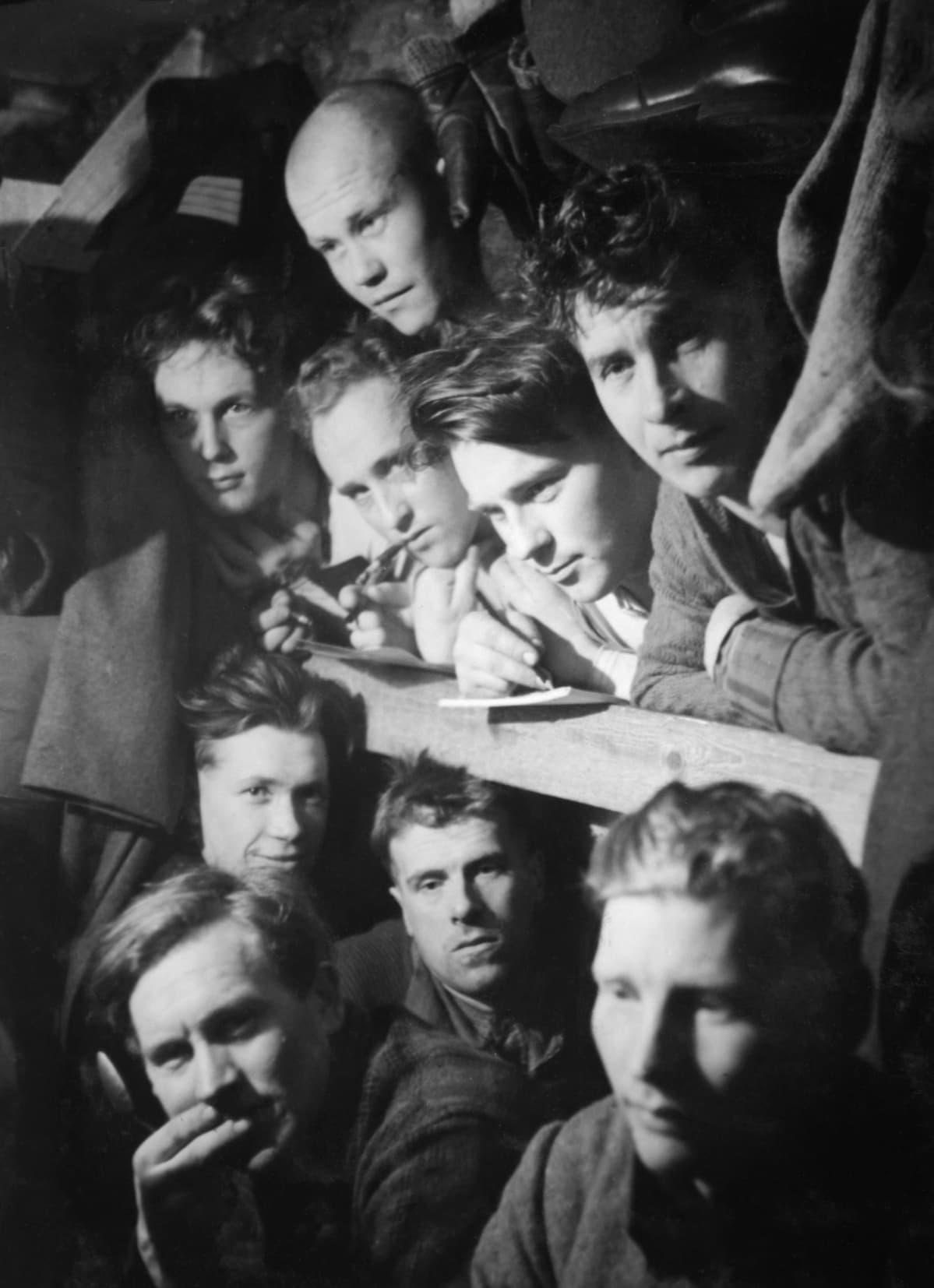 Yhdeksän sotilasta ahtaa kasvonsa samaan korsussa otettuun valokuvaan.