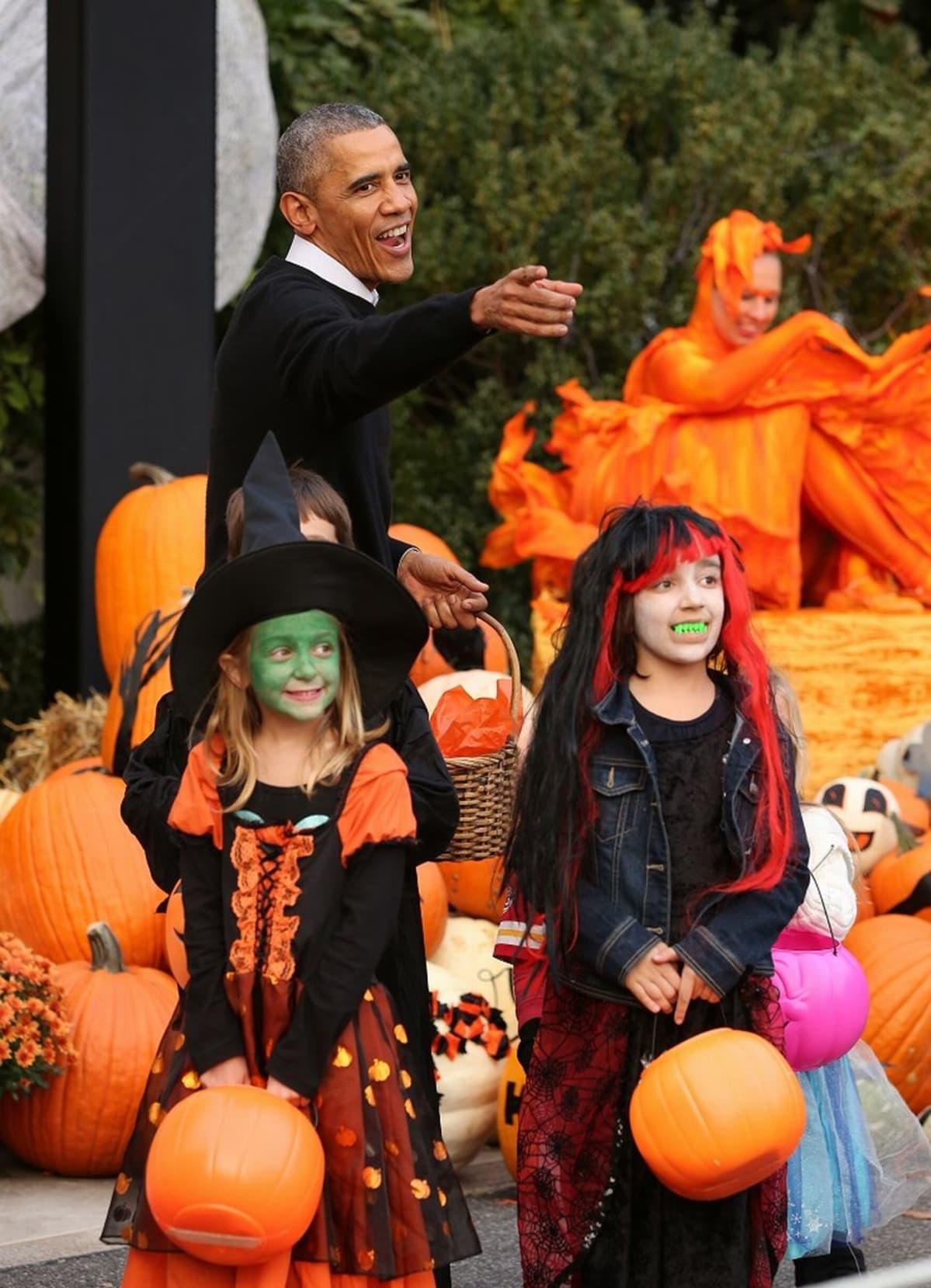 Kaksi noidiksi pukeutunutta pikkutyttöä ja presidentti Barack Obama, jolla on kädessään pajukori. Ympärillä kurpitsoja.