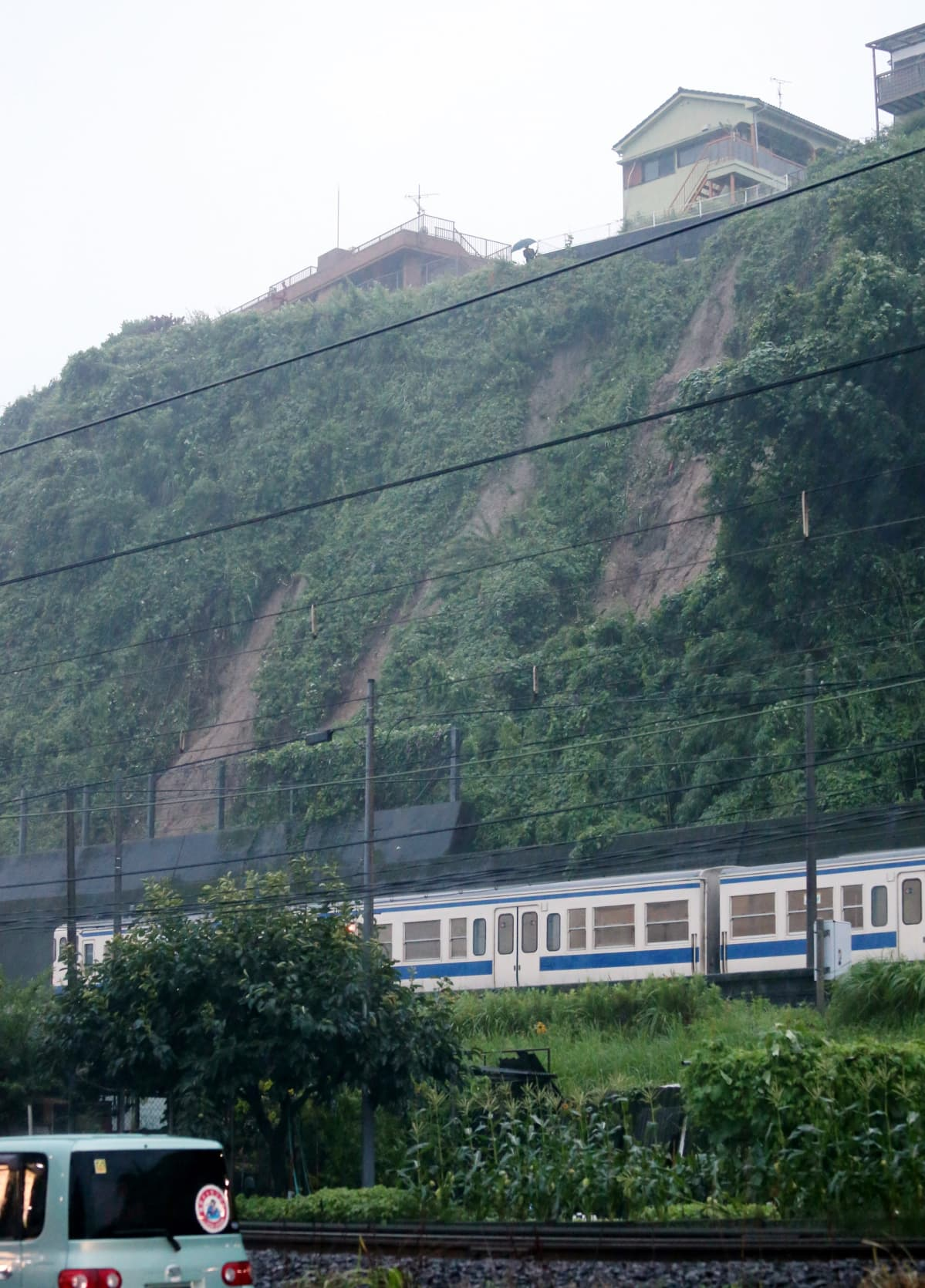 Rankkasateiden pelätään aiheuttavan tuhoisia maanvyöryjä Japanissa. Tässä juna Minami-Kagoshiman asemalla, maanvyörymän vieressä keskiviikkona.