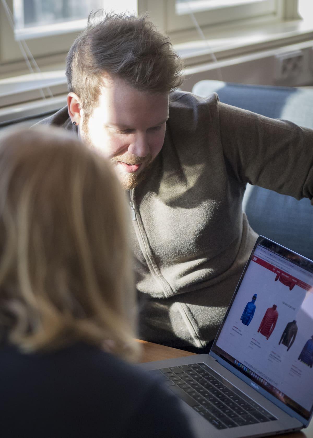 Kaksi miestä katselee kannettavaa tietokonetta