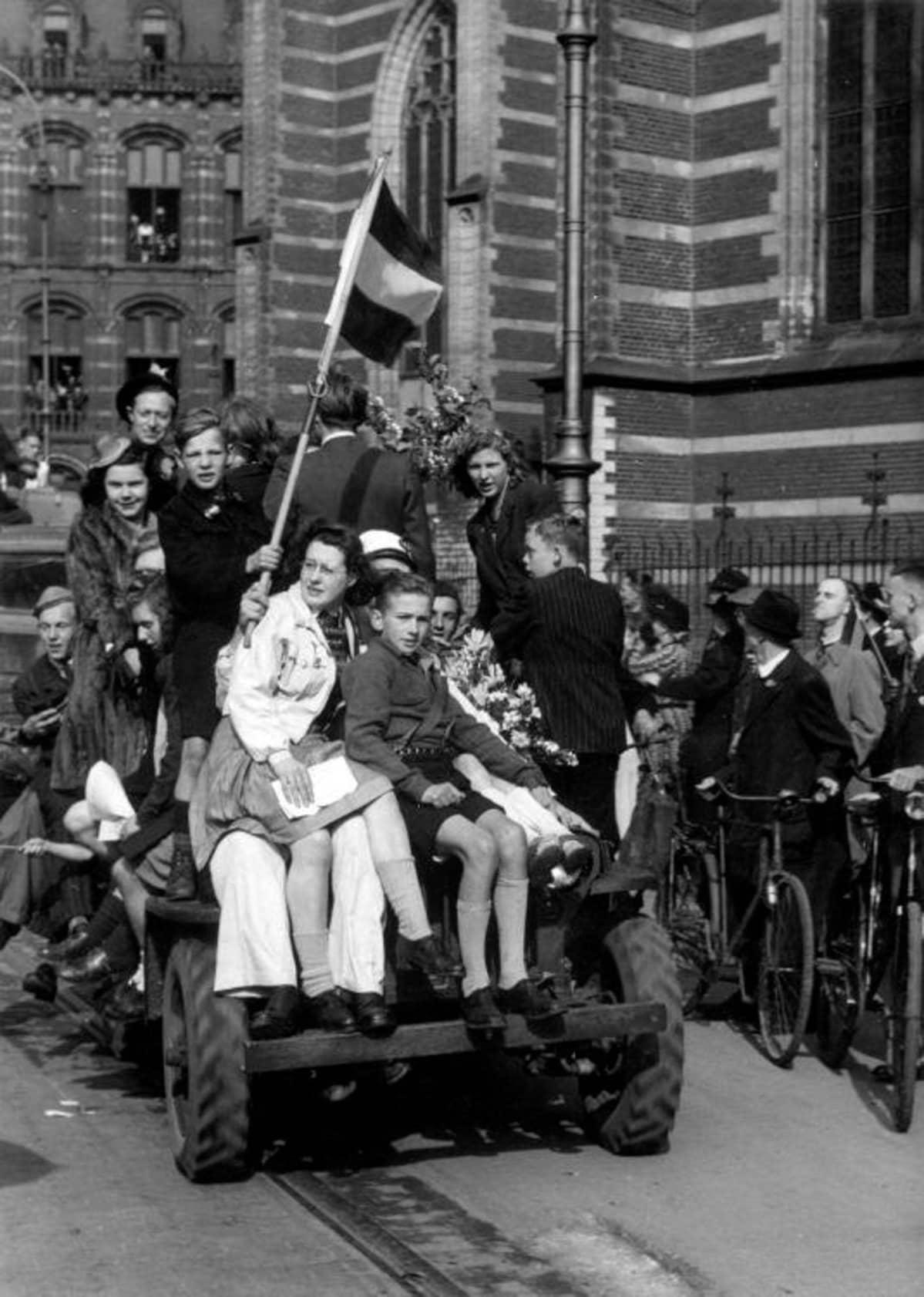 Kymmenkunta ihmistä maastoauton kyydissä, pikkupoika heiluttaa lippua.