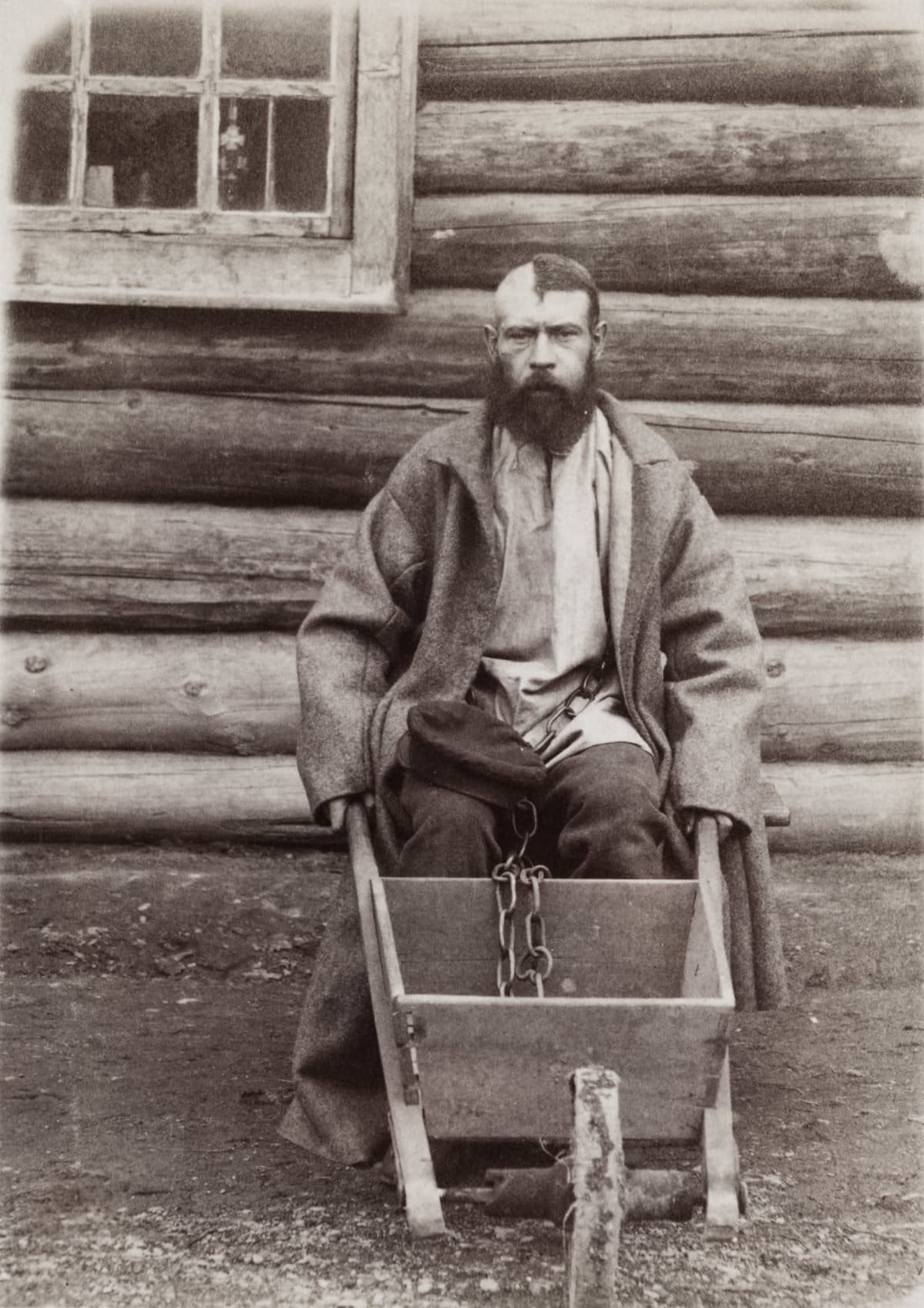 Vanki kahleissa kottikärryn kanssa 1898. Päälaki puoliksi ajeltu vangin merkiksi.