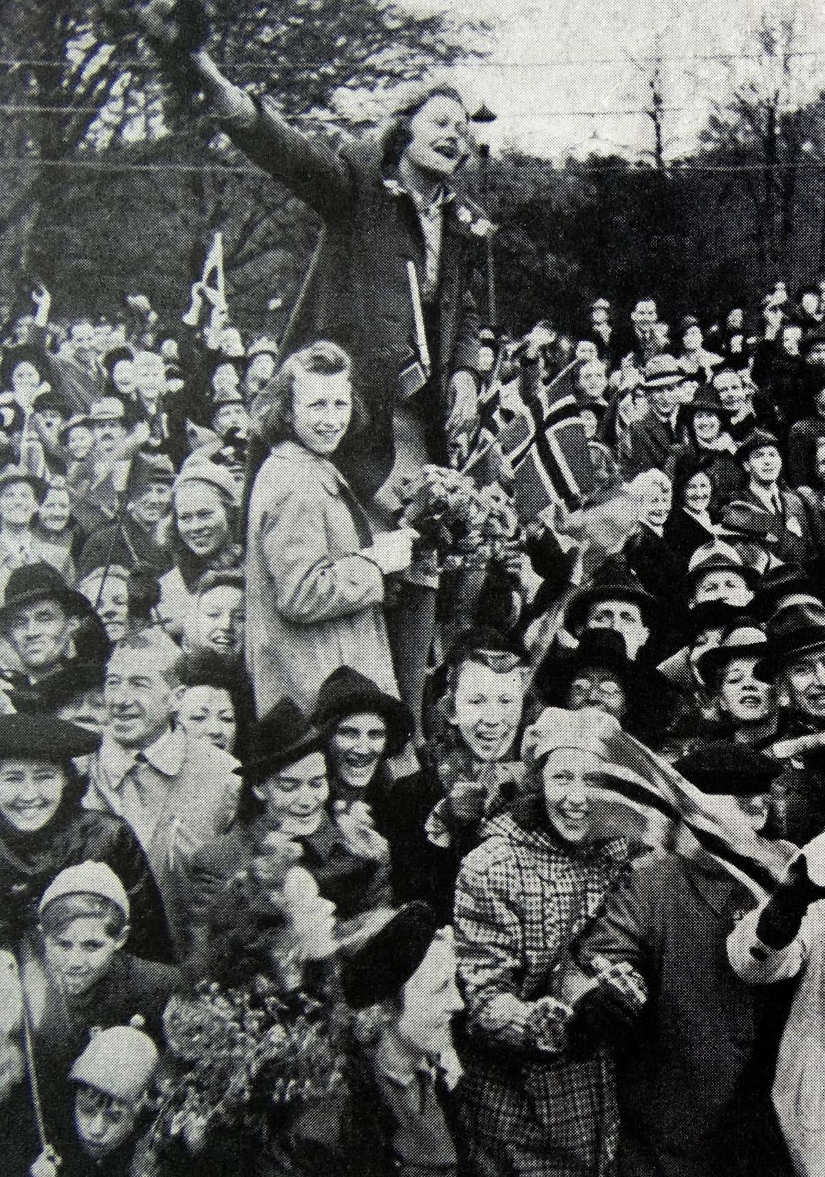Nainen ja tyttö seisovat korokkeella ihmisjoukossa, tytöllä kädessä Norjan lippu.