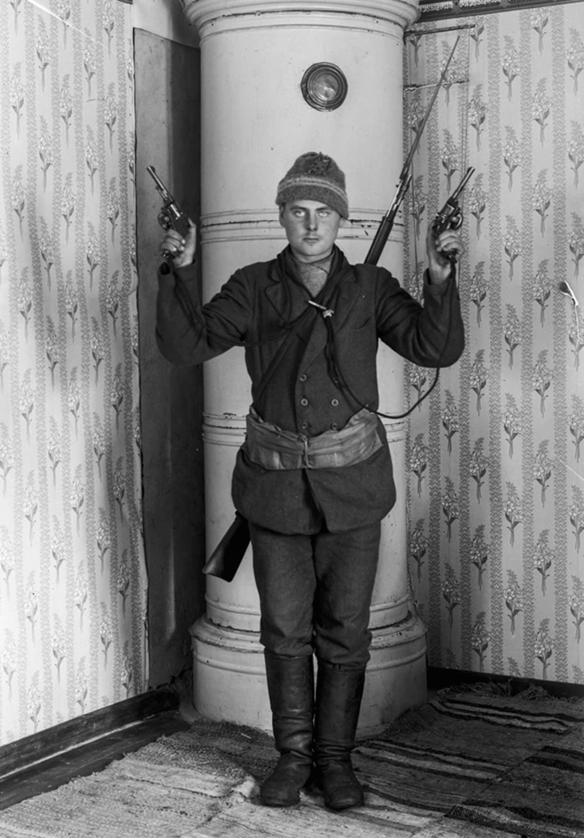 Punakaartilainen esittelee aseistustaan.