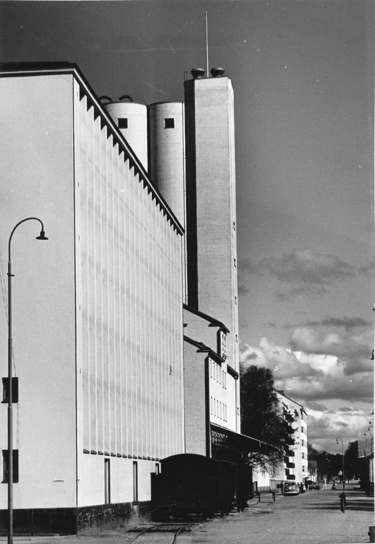 Näkymä Mannerheimintieltä 1960-1970-luvulta. Etualalla vasemmalla on SOK:n konttori- ja varastorakennus, jonka vieressä valssimylly. taustalla kohoavat viljasiilot.