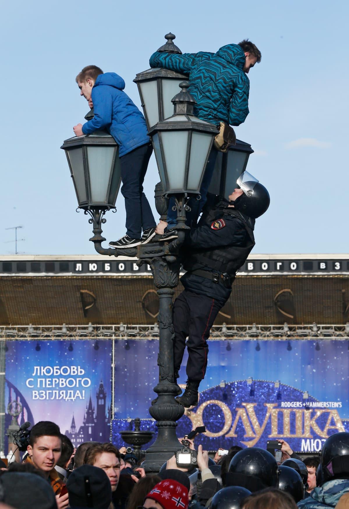 Erikoisjoukkojen poliisi kiipesi katulamppuun mielenosoittajien perässä sunnuntaina 26. maaliskuuta 2017.