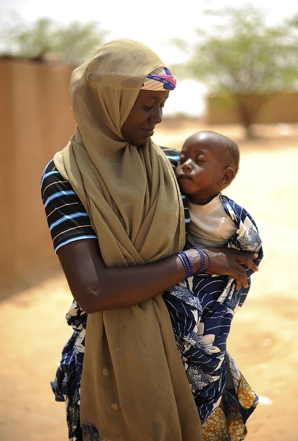 Äiti kantaa nukkuvaa lasta sylissään.