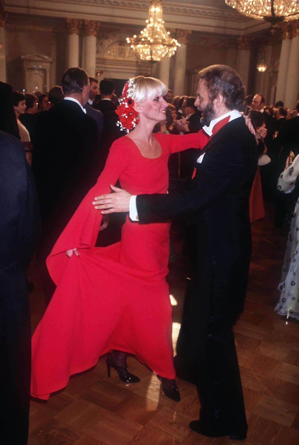 Vuoden 1977 vastaanotolla Marjatta Sarpaneva ihastutti veistoksellisessa punaisessa puvussa puolisonsa Timo Sarpanevan rinnalla.