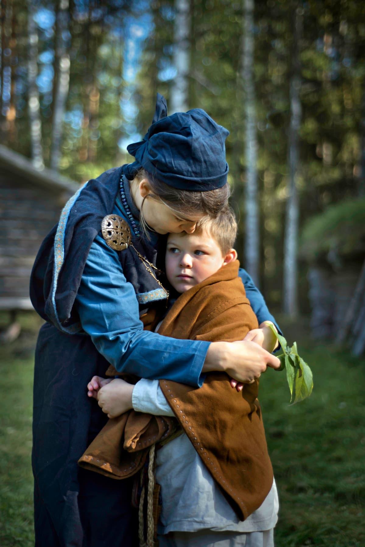 Viikinkiajan asuun pukeutunut äiti rutistaa poikaansa sylissään.