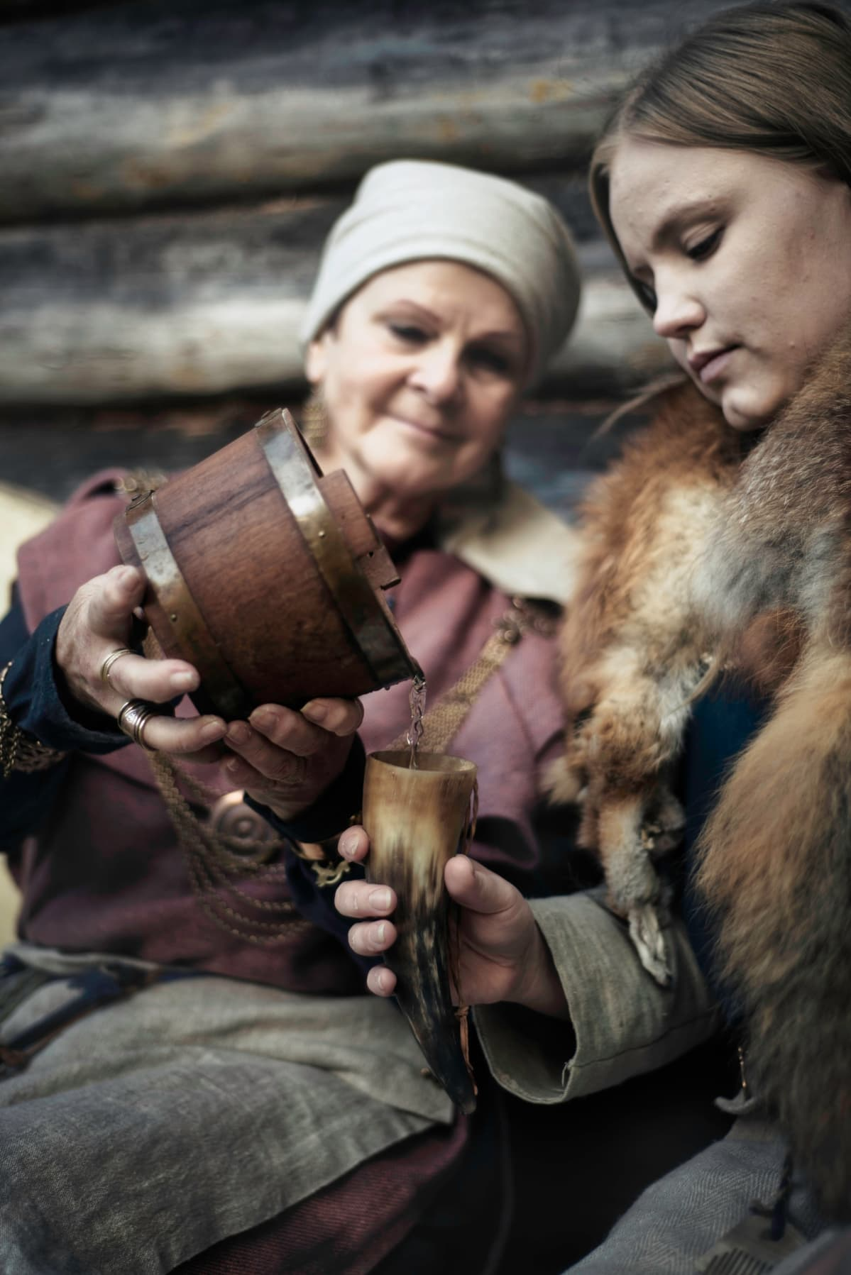 Vanhempi nainen kaataa nuoremmalle naiselle juomaa juomasarveen.