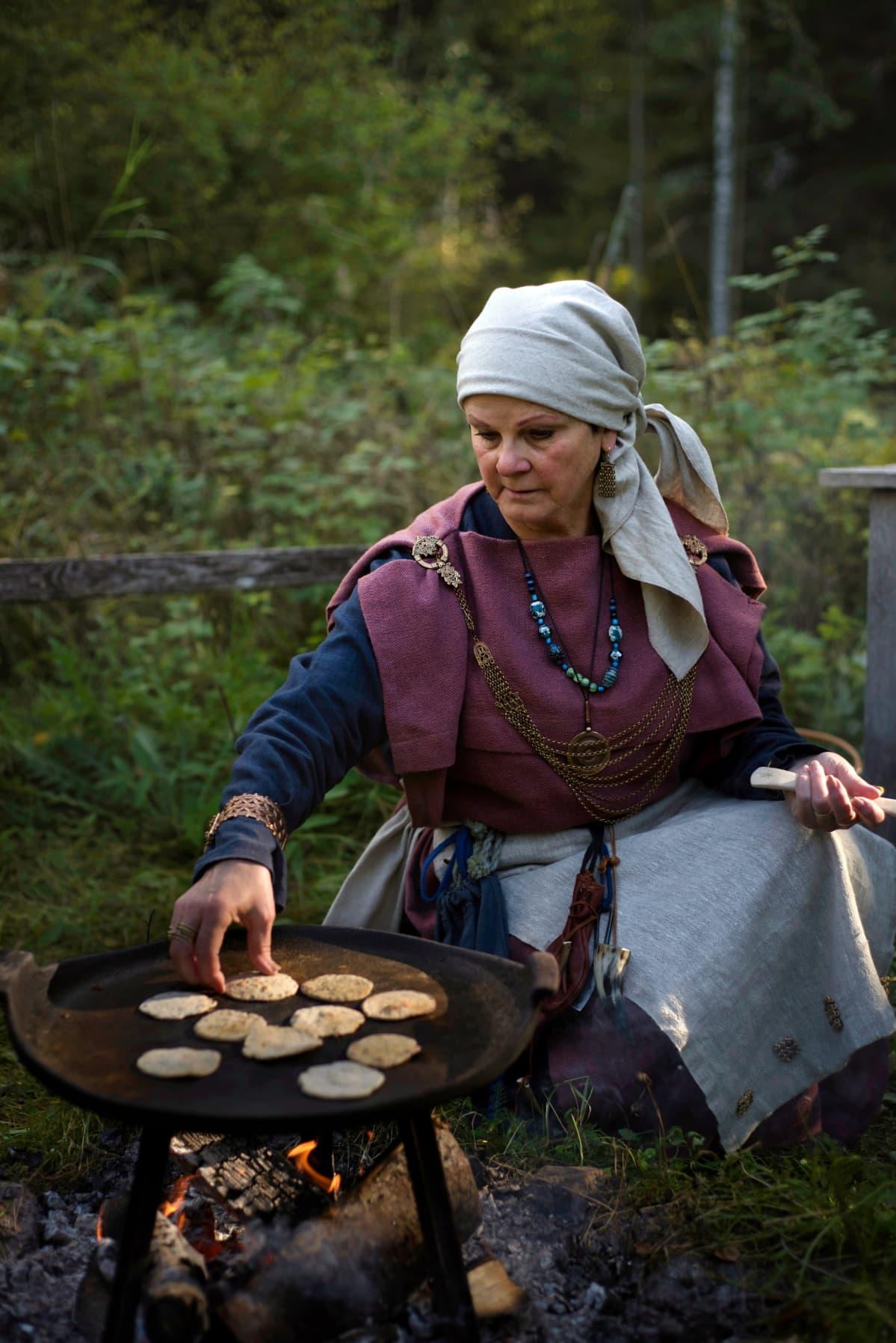 Rautakautiseen asuun pukeutunut nainen paistaa leipäsiä.