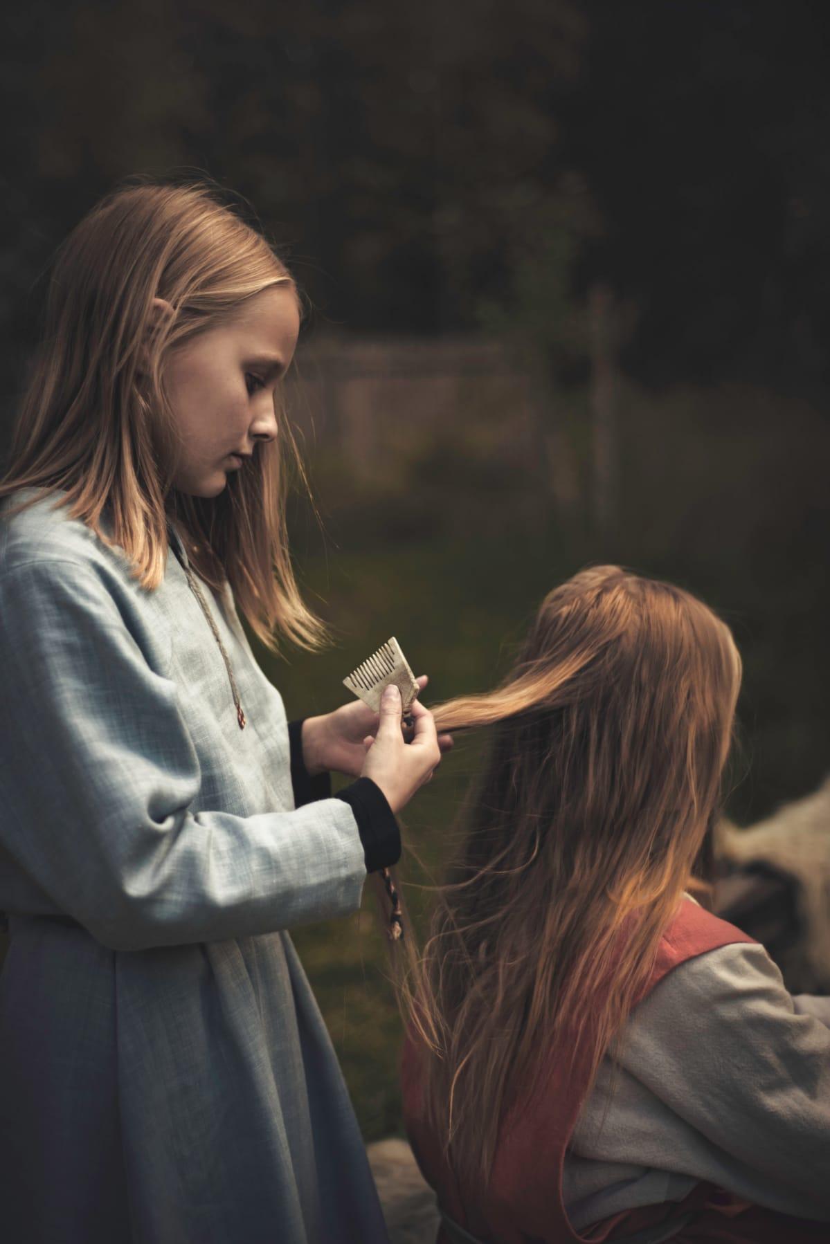 tyttö kampaa toisen tytön hiuksia