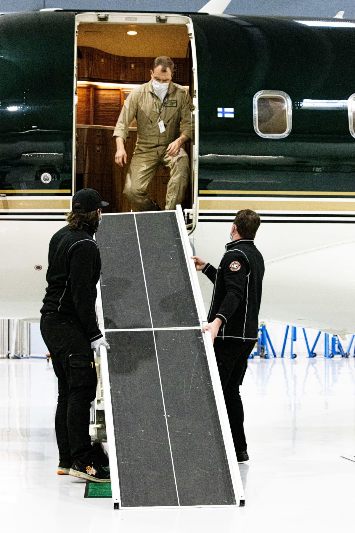 Kapteeni Antti Saarinen ottaa vastaan lentokoneessa kiinnitettävää nostosiltaa jonka avulla saadaan potilas tuotua koneeseen.