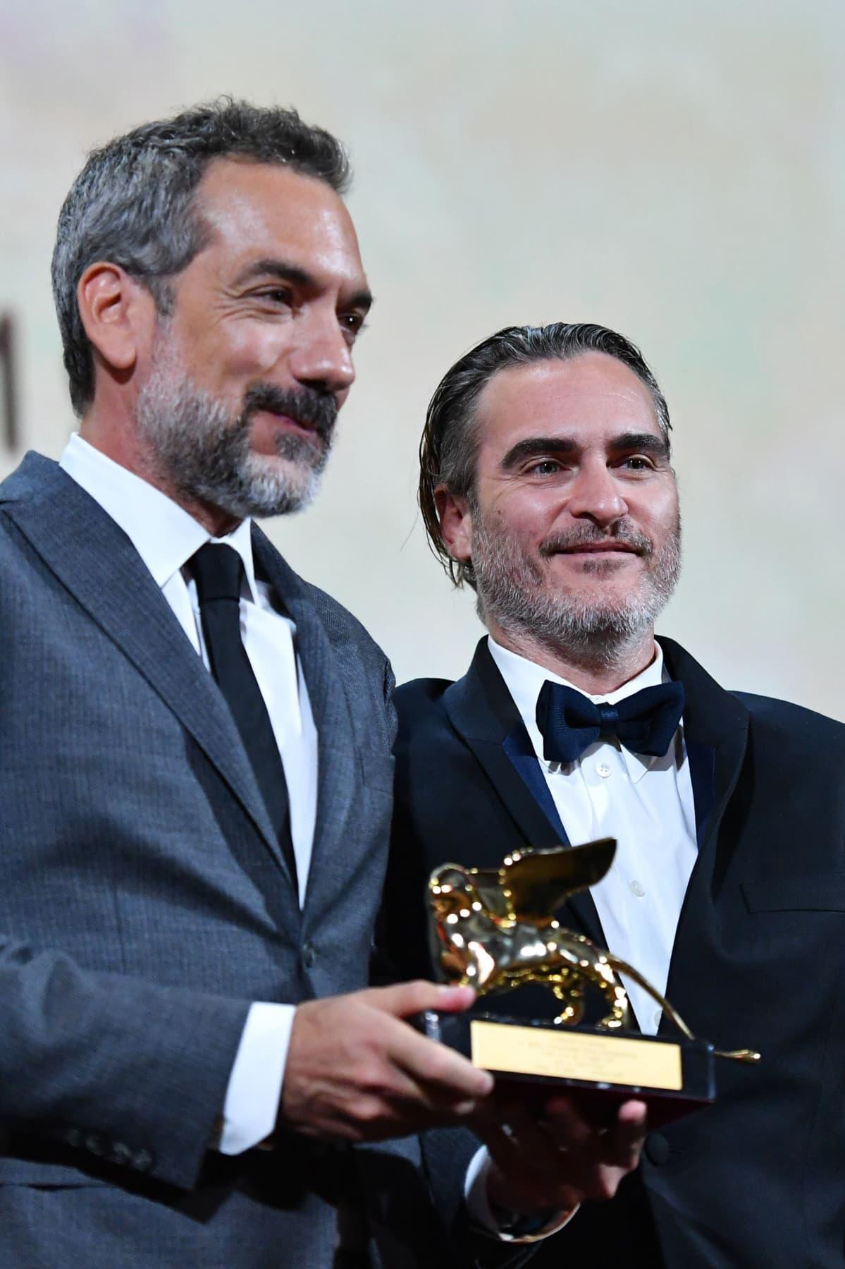Yhdysvaltalaisohjaaja Todd Phillips (vas.) ja näyttelijä Joaquin Phoenix vastaanottivat Venetsian elokuvajuhlien pääpalkinnon elokuvallaan 'Joker' Lidon saarella 7. syyskuuta.