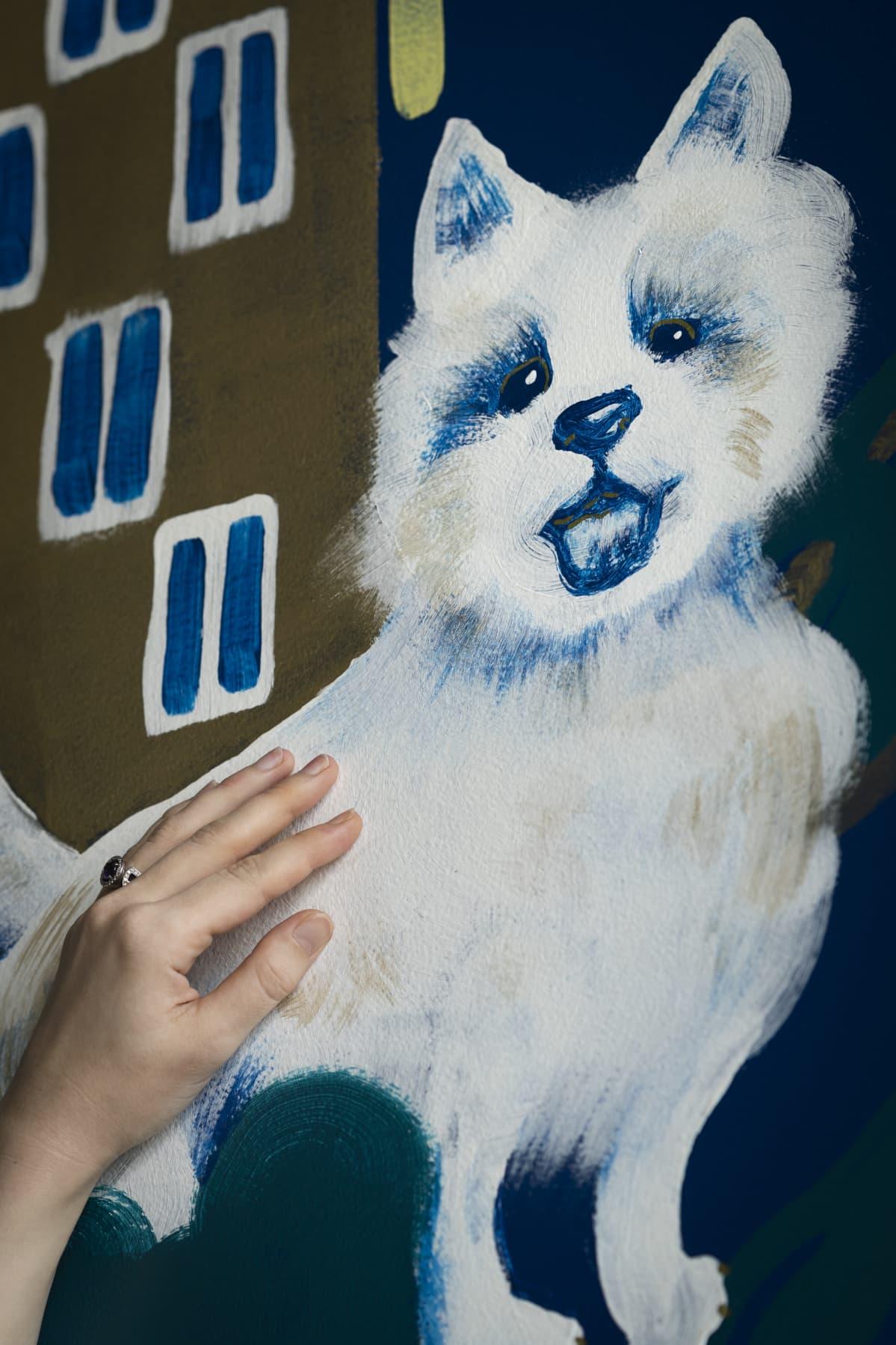 Käsi silittää seinään maalattua koiran kuvaa.