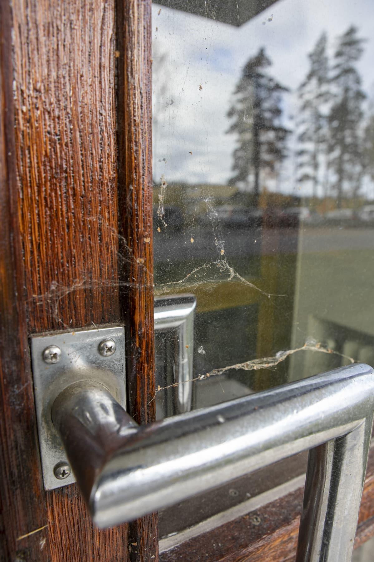 Hämähäkin seittiä käyttökiellossa olevan rakennuksen oven kahvassa.
