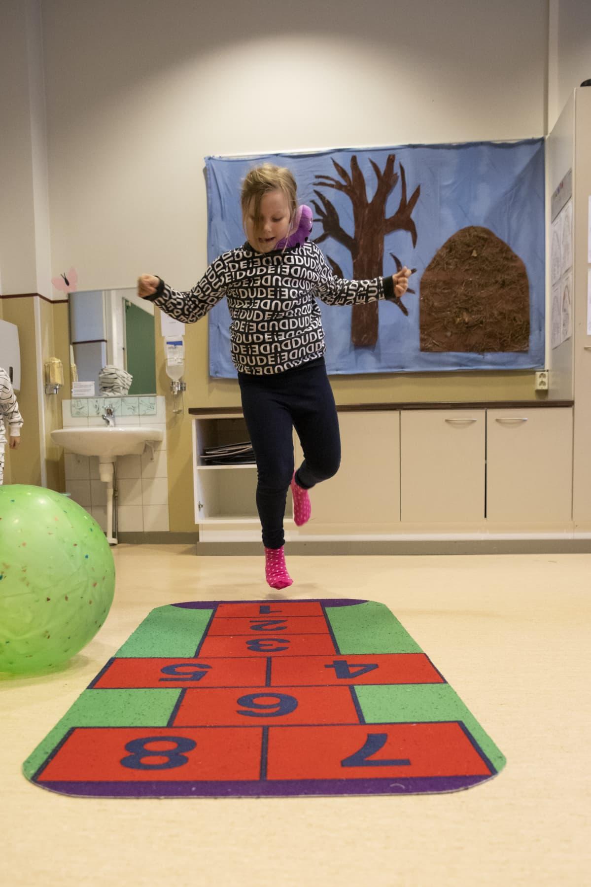 Lapsi hyppimässä ruutua päiväkodin leikkihuoneessa.