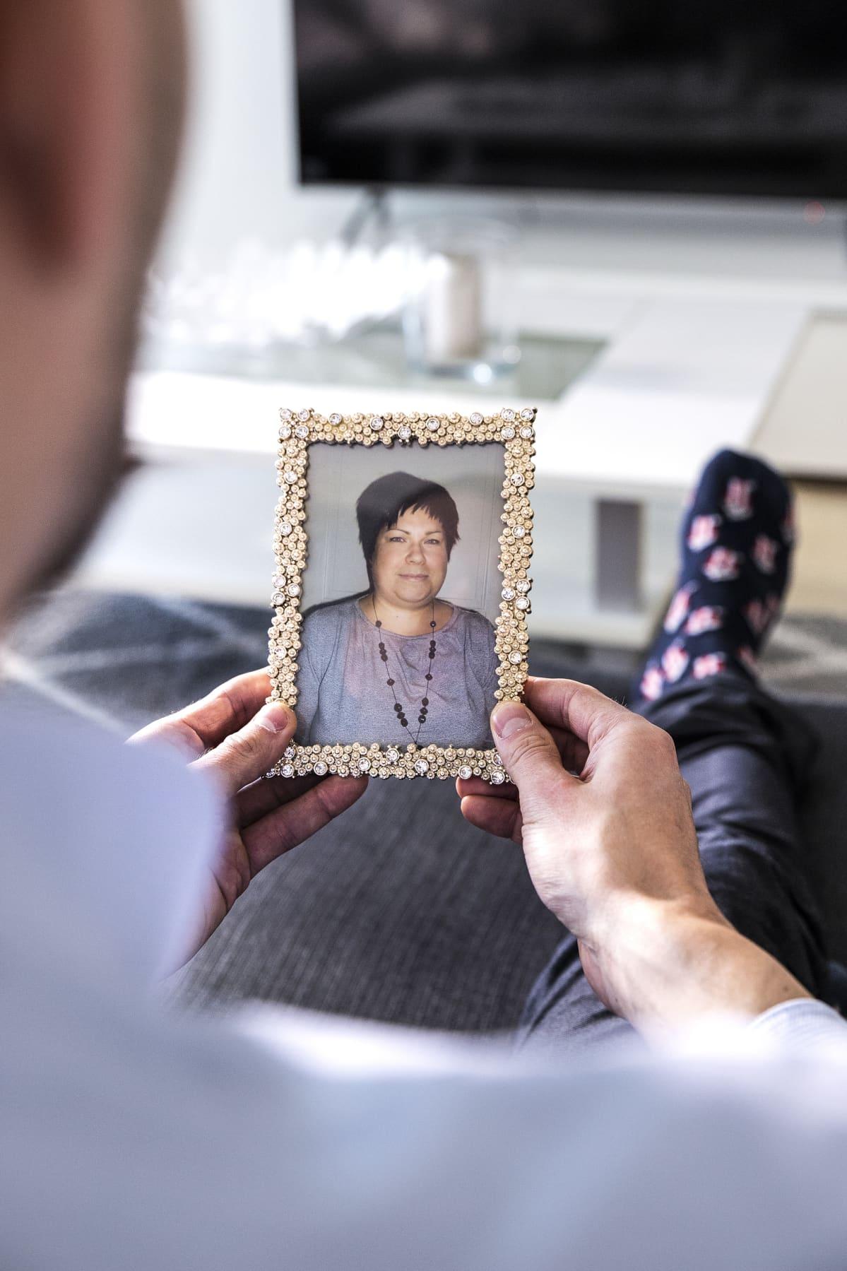 Mies katsoo valokuvaa