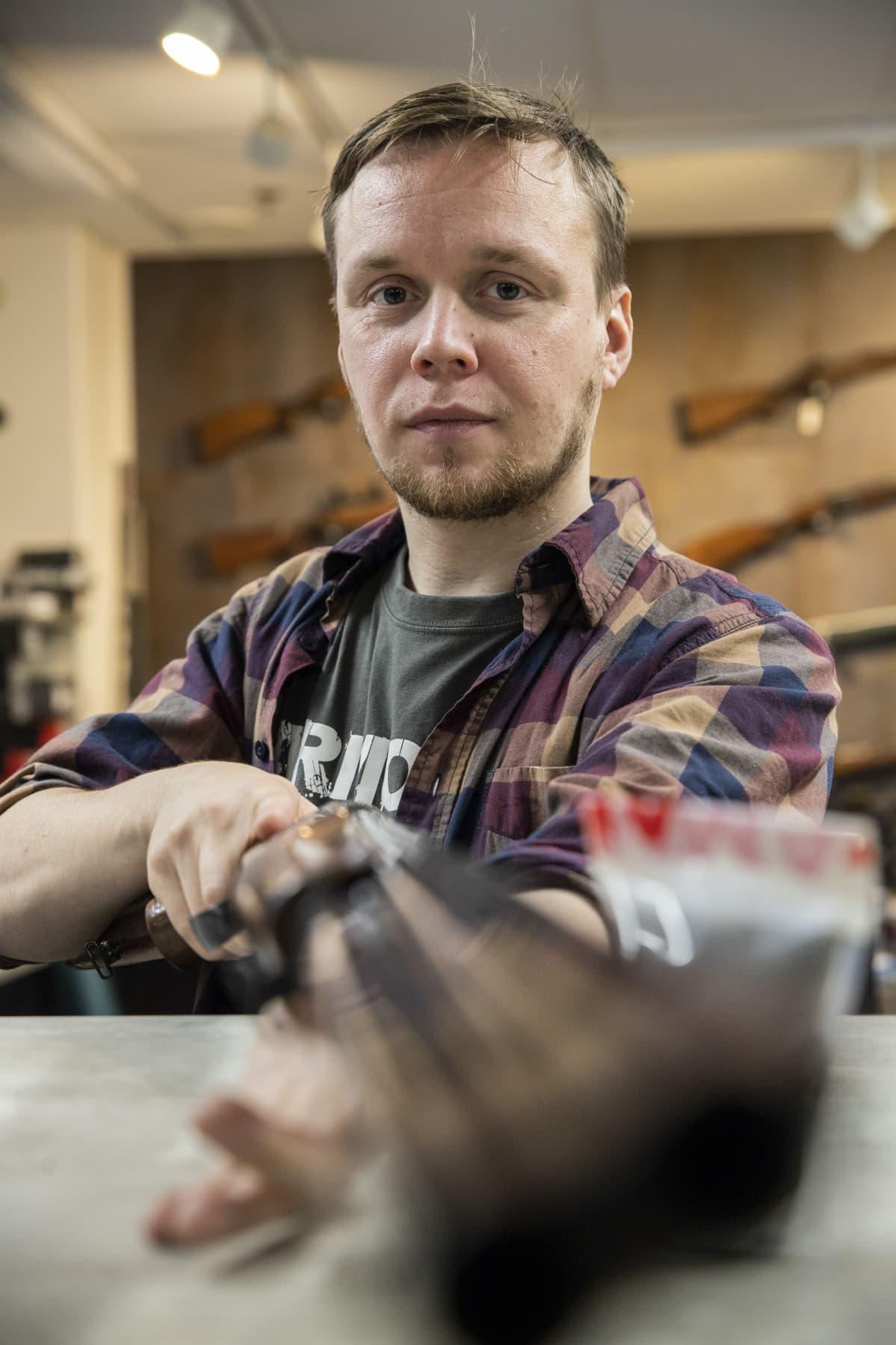 Armoria ase-liikkeen yrittäjä Vesa-Matti Iskanius käsittelee haulikkoa liikkeessään.
