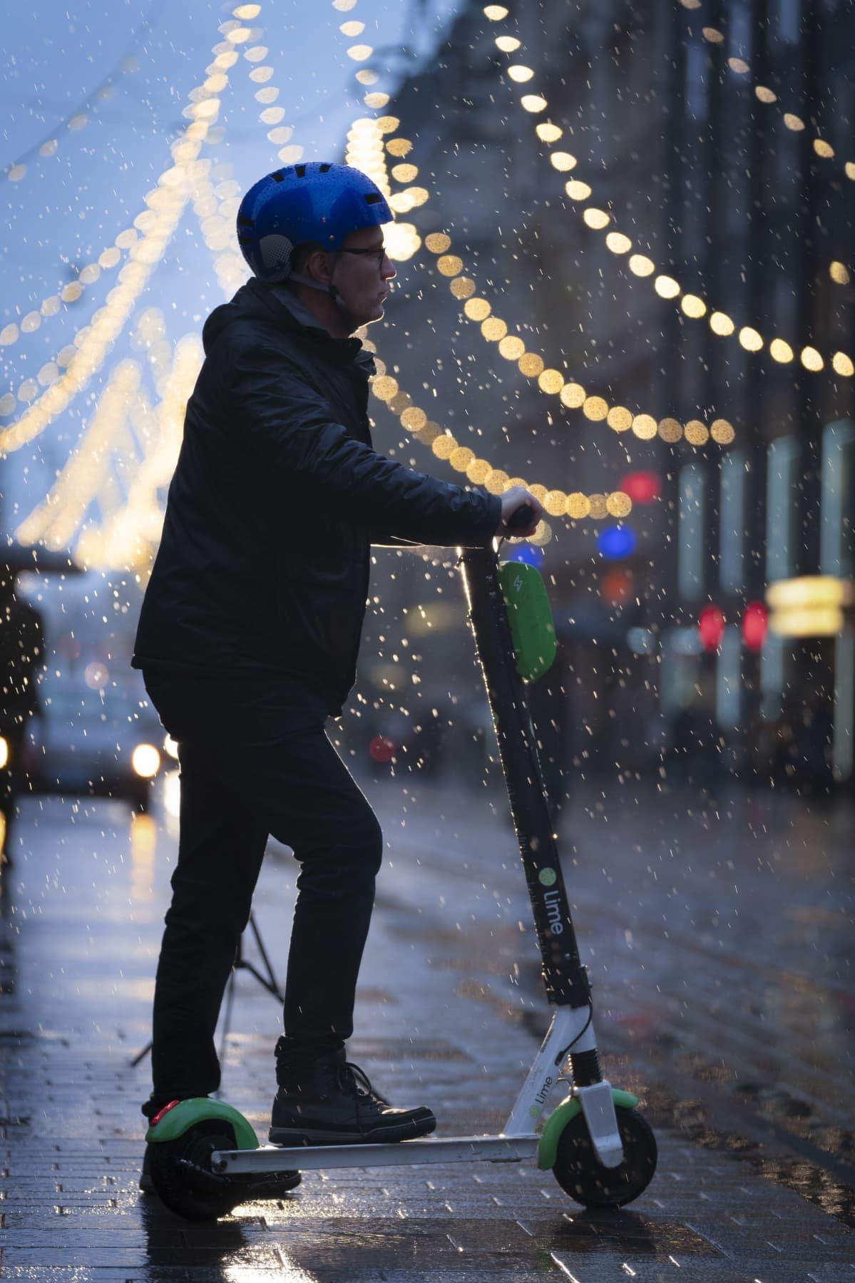 Sähköpotkulautailija hämärällä sateessa Helsingin Aleksanterinkadulla.