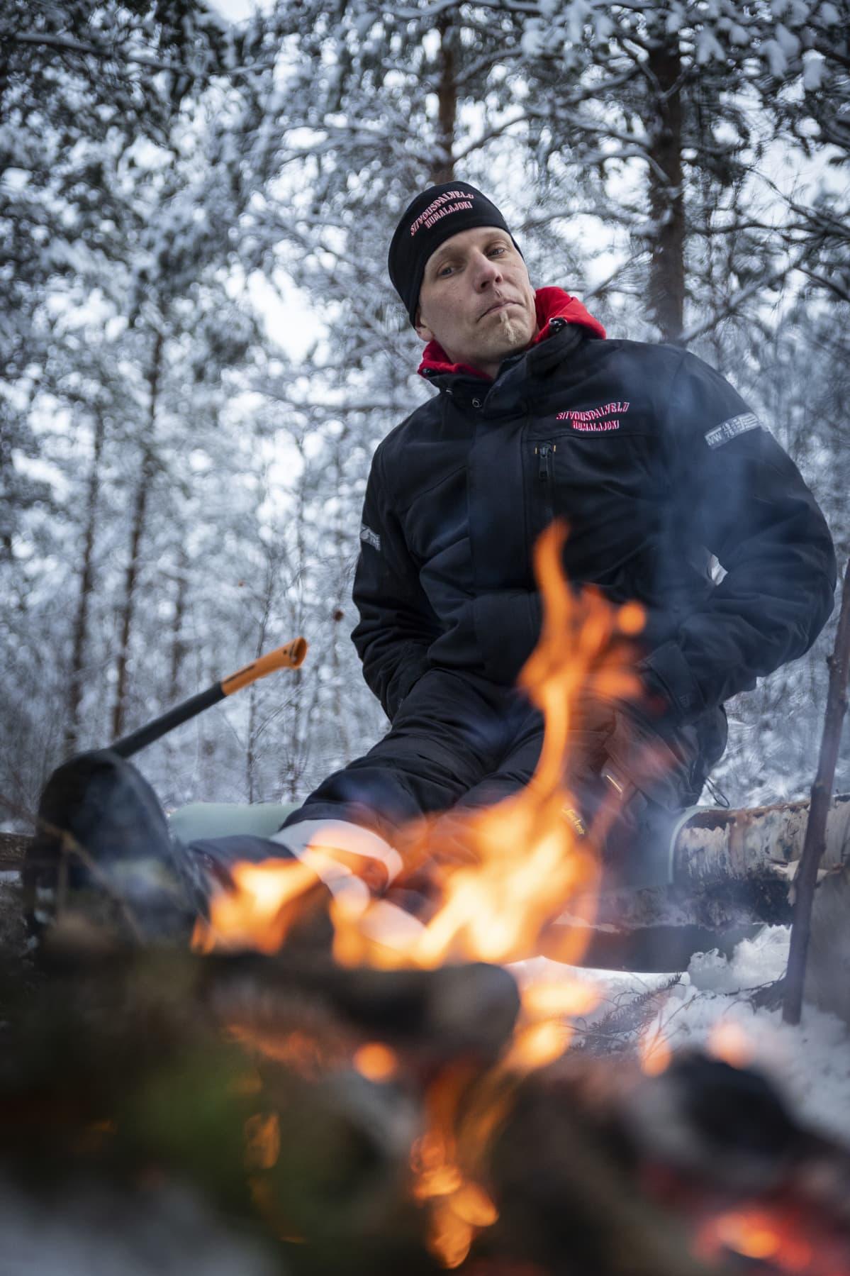 Antti Humalajoki istuu nuotion ääressä.