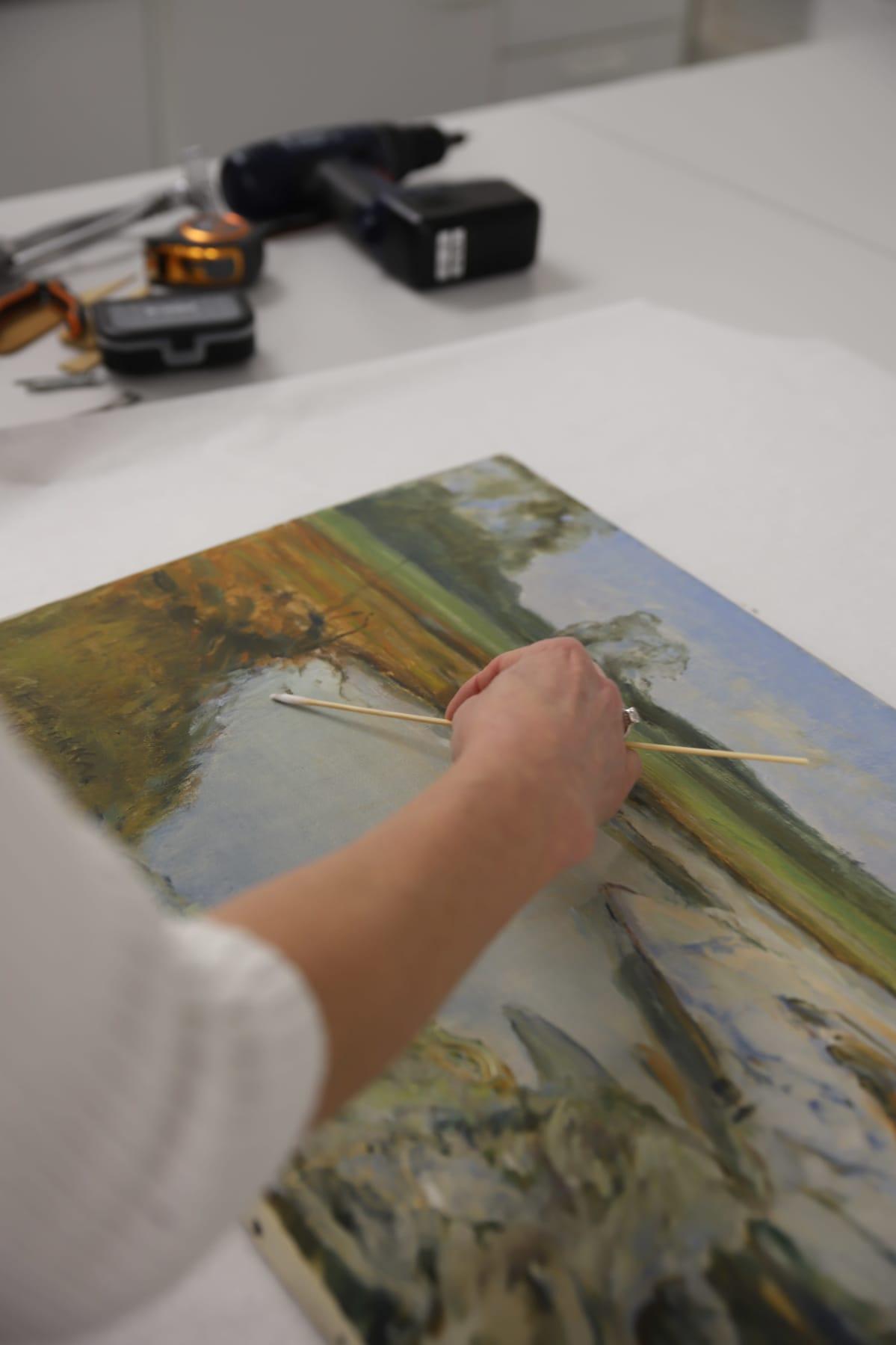 taidekonservaattori puhdistaa maalauksen pintaa