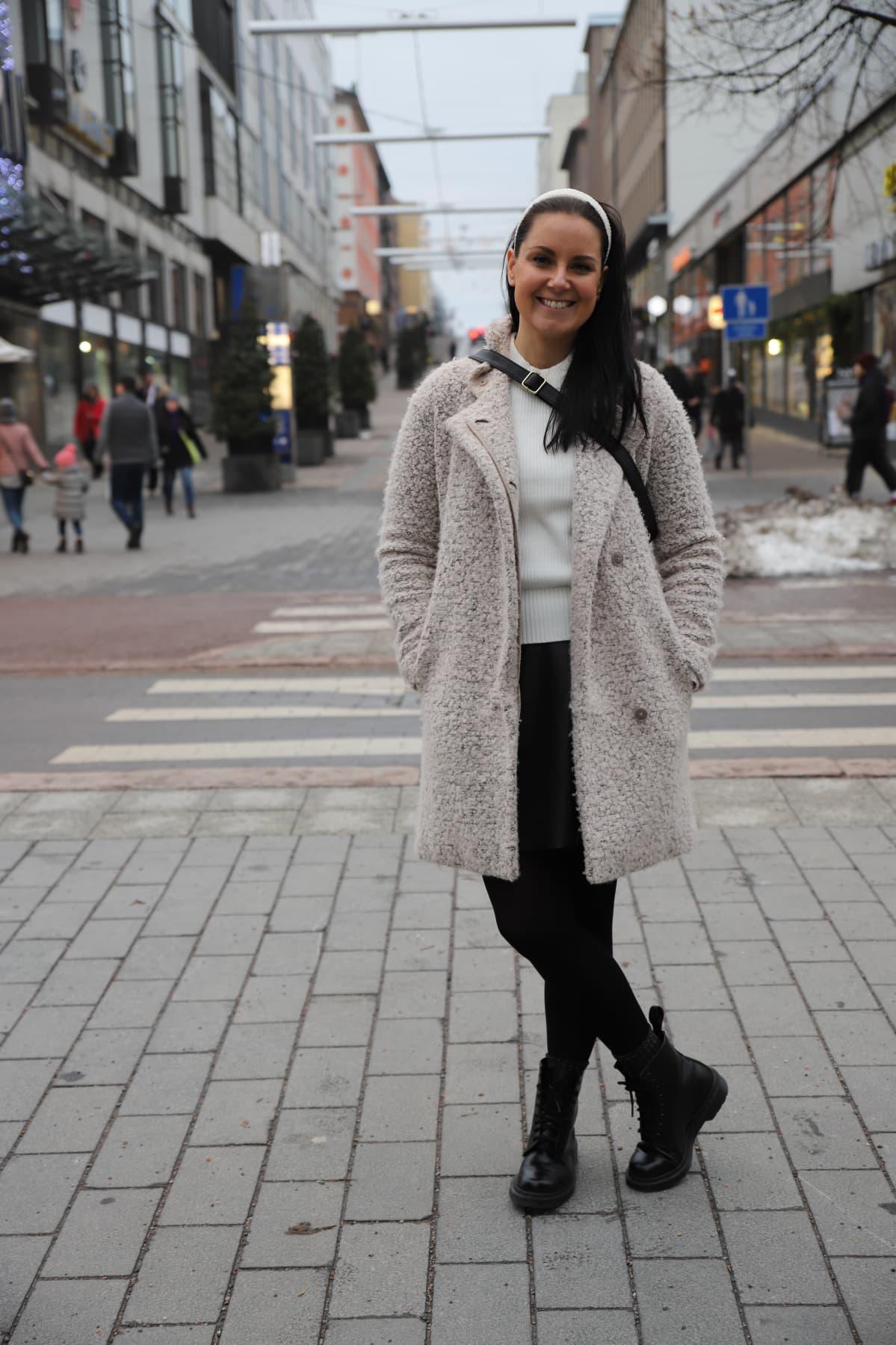 Nuori nainen seisoo kadulla ja hymyilee