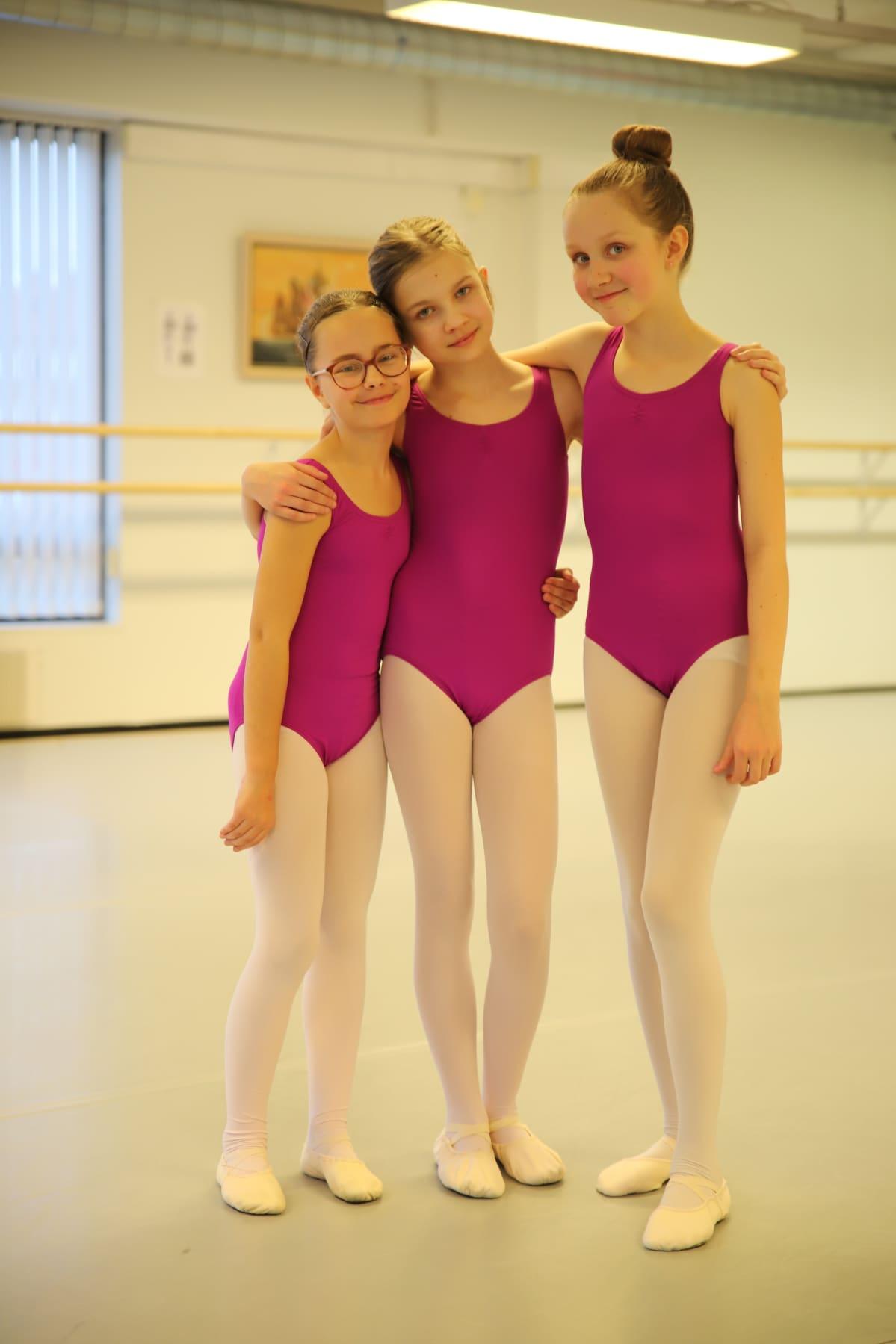 Etelä-Hämeen Tanssiopsiton oppilaat Inna Heikkinen, Ronja Laitinen ja Linnea Valtanen poseeraavat balettiitunnin jälkeen tanssisalissa.