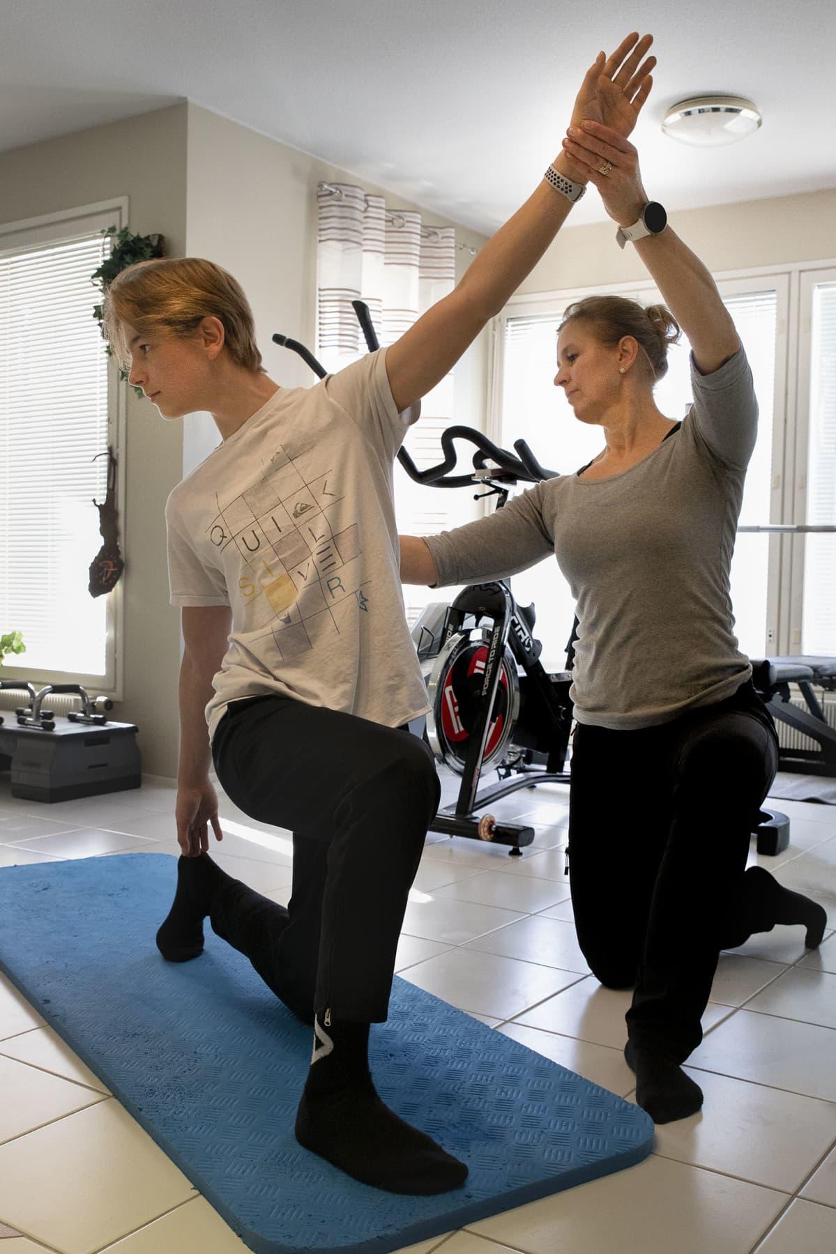 Äiti opettaa pojalleen liikuntaa kotona etäkoulussa.