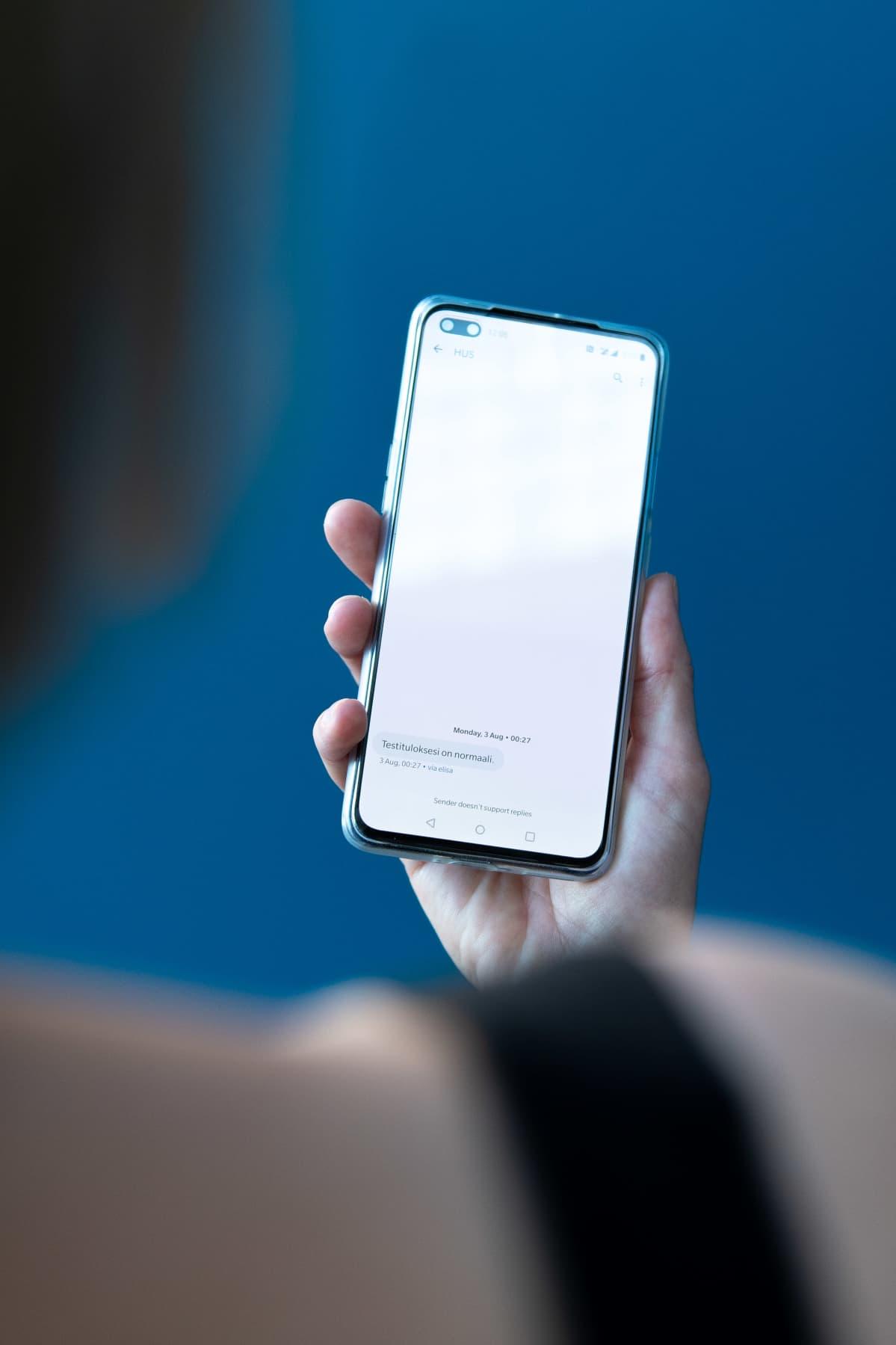 Nainen pitää puhelinta sinisen taustan edessä, puhelimen näytöllä näkyy tekstiviesti jossa kerrotaan koronatestin tulos.