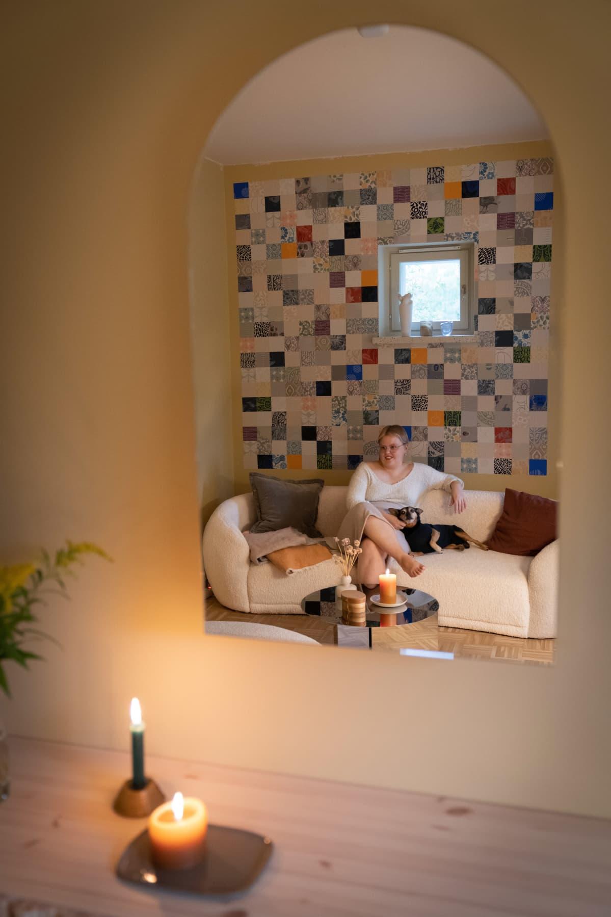 Vilja Jääskeläinen sohvallaan koiran kanssa.