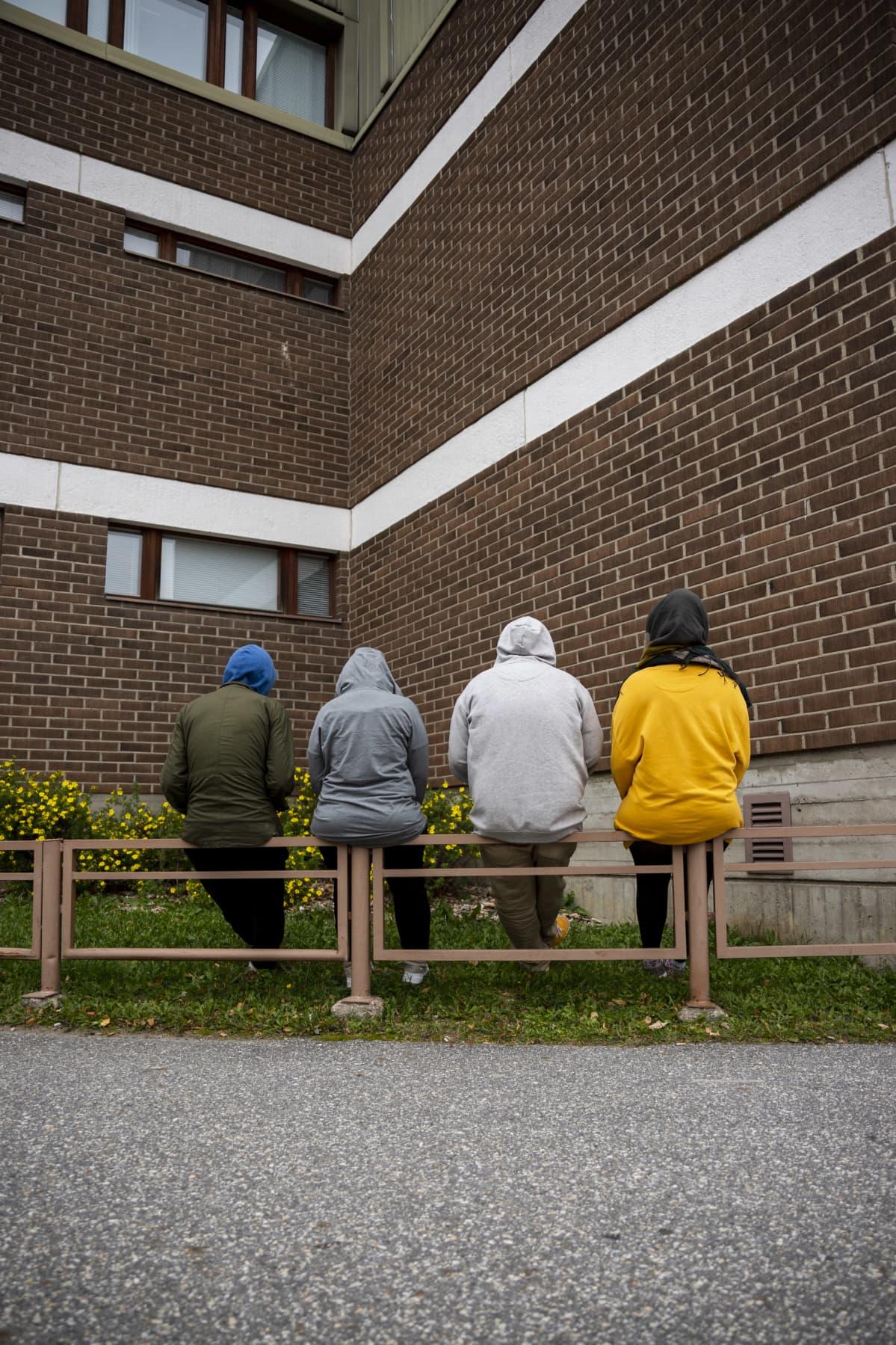 Neljä tunnistamatonta henkilöä istuu penkillä.