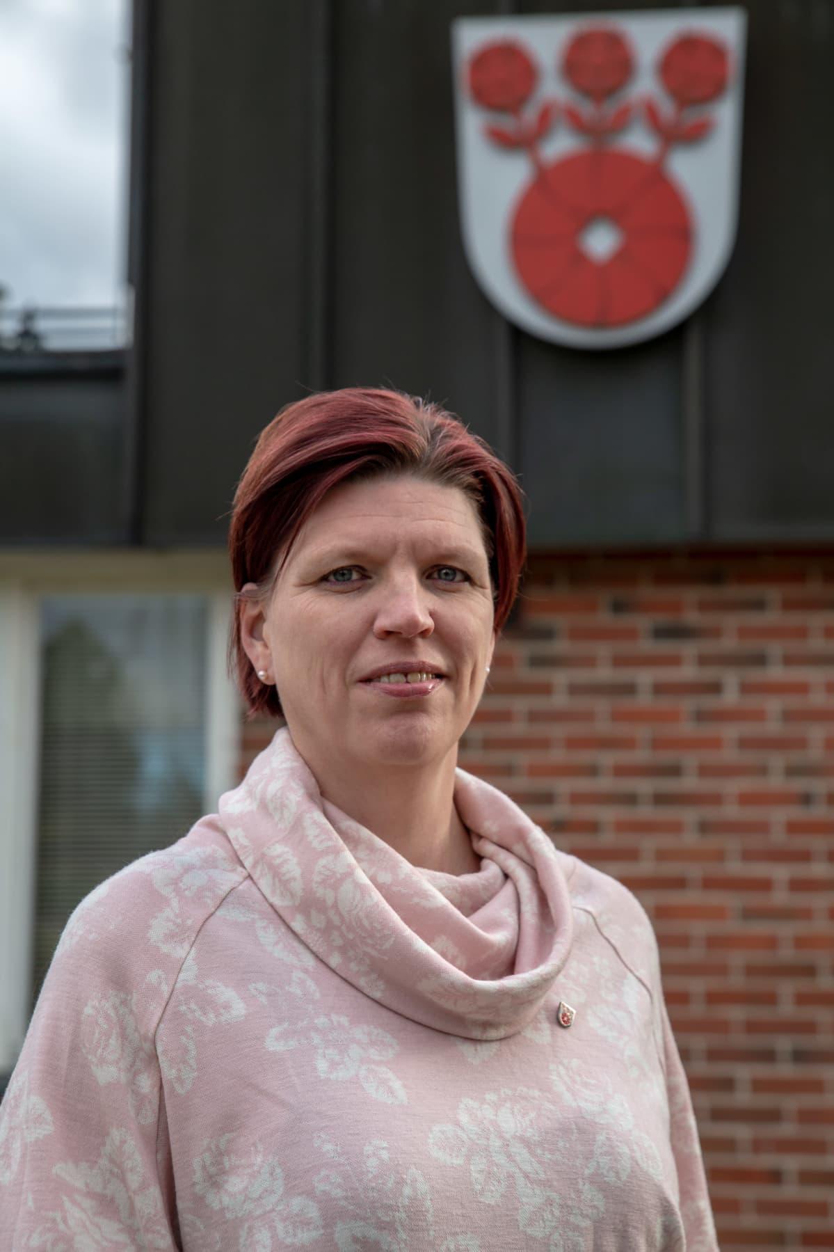 Valtuuston puheenjohtaja Sanna Kurki seisoo Askolan kunnantalon edessä ja katsoo kameraan. Kunnan vaakuna näkyy taustalla kunnantalon seinällä.