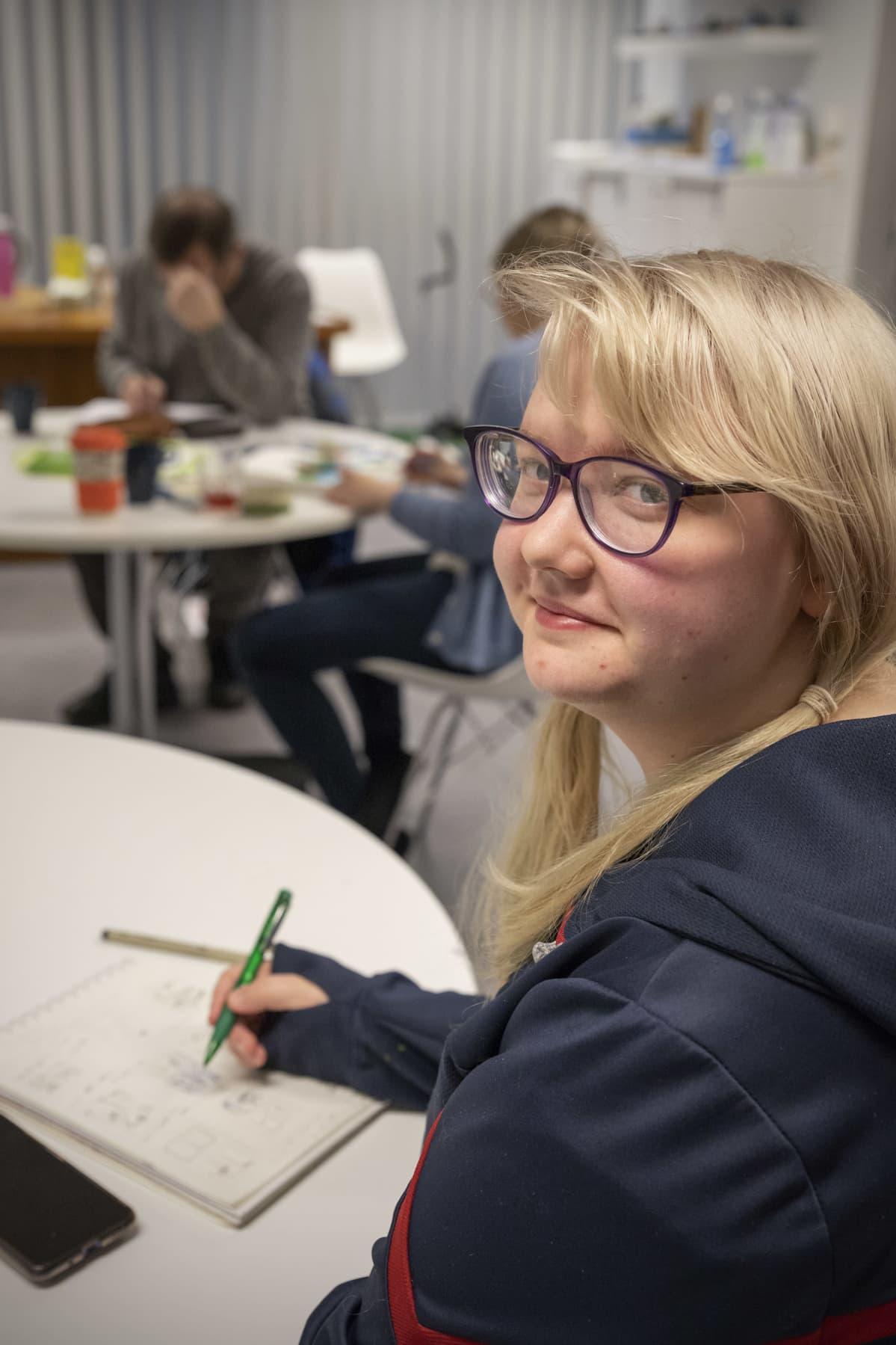 Lili Peltola piirtää sarjakuvaa Joensuun sarjakuvaseuran sarjisillassa.