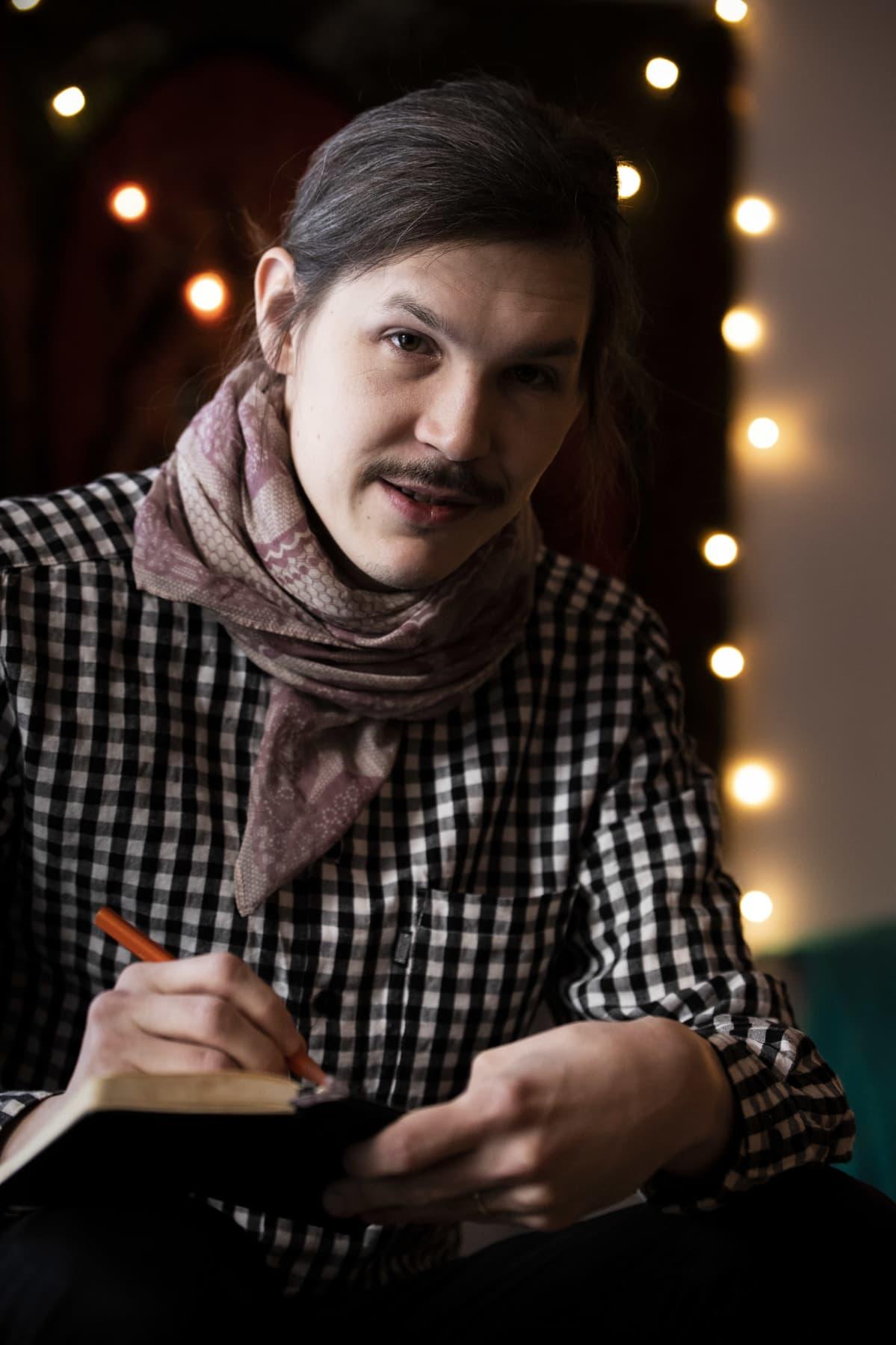 Joonatan Tola kirjoittaa muistikirjaa