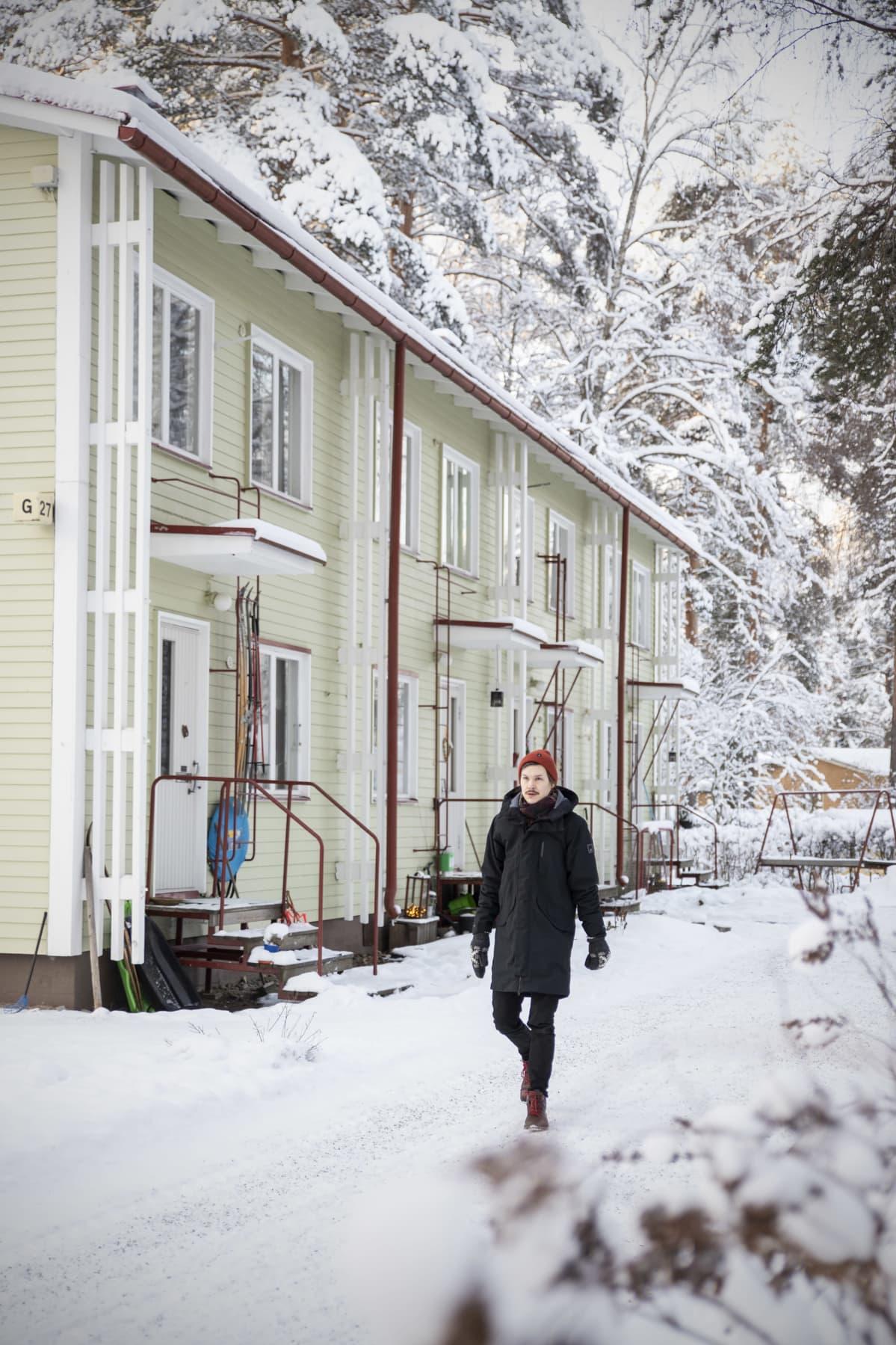 Joonatan Tola kävelee lumisella kotipihalla