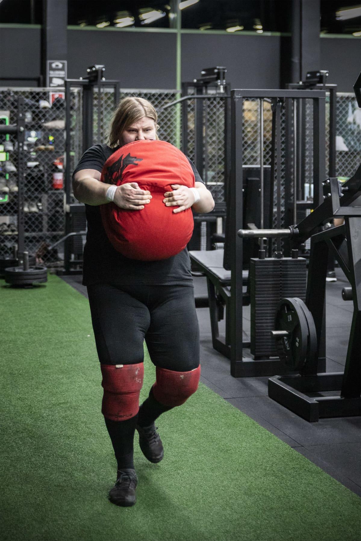 Salla Romo kantaa painavaa punaista säkkiä.