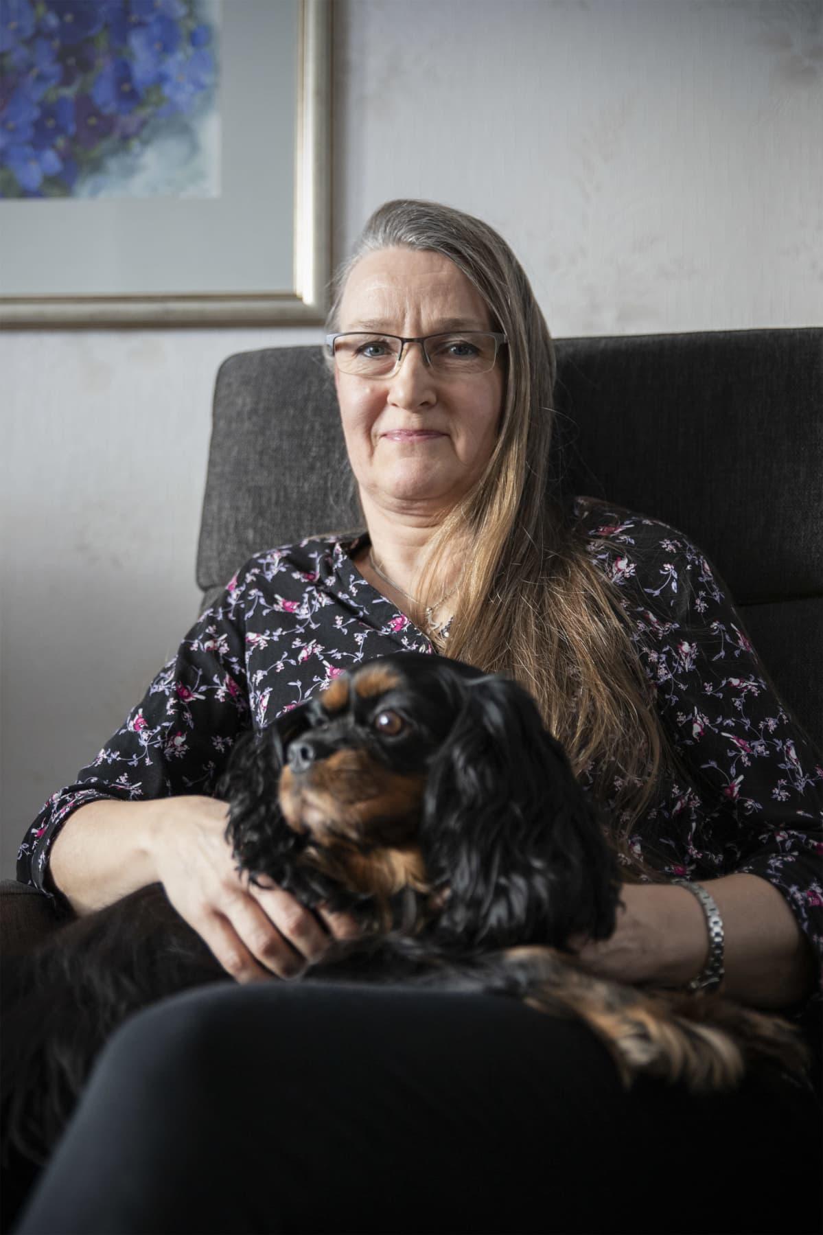 Tuula Porkka istuu nojatuolissa musta Heta-koira sylissään.
