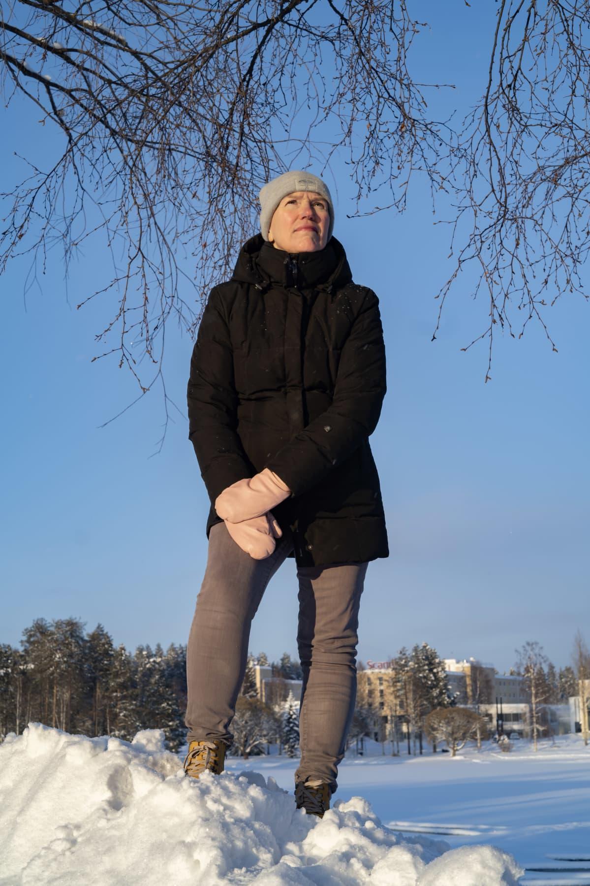 Kainuun liiton viestintäpäällikkö Sari Eskelinen lumikasan päällä, taustalla kaukaveden uimahalli.